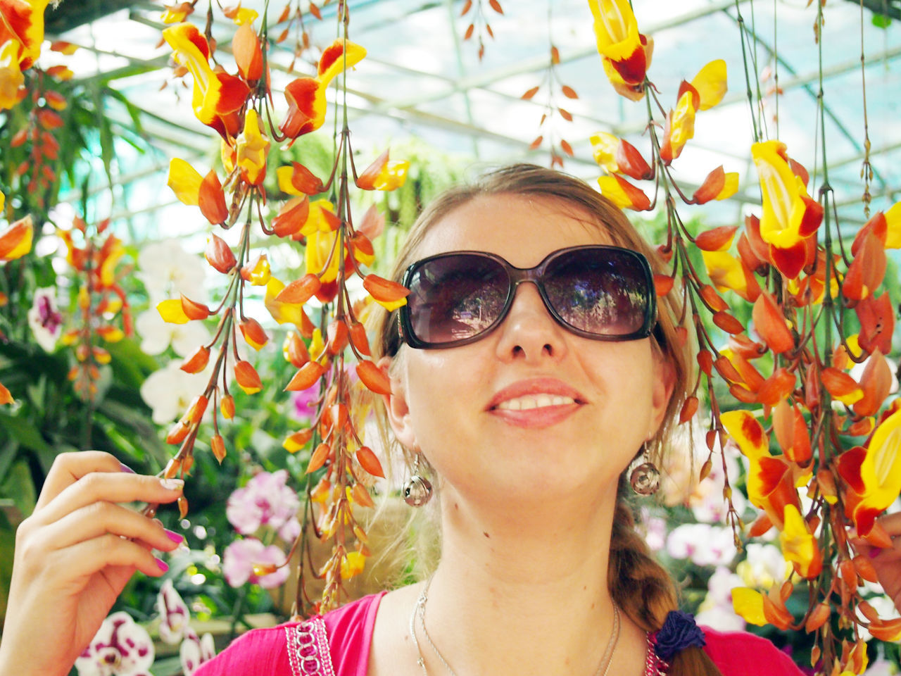Young Woman Wearing Sunglasses Amidst Orchids In Greenhouse