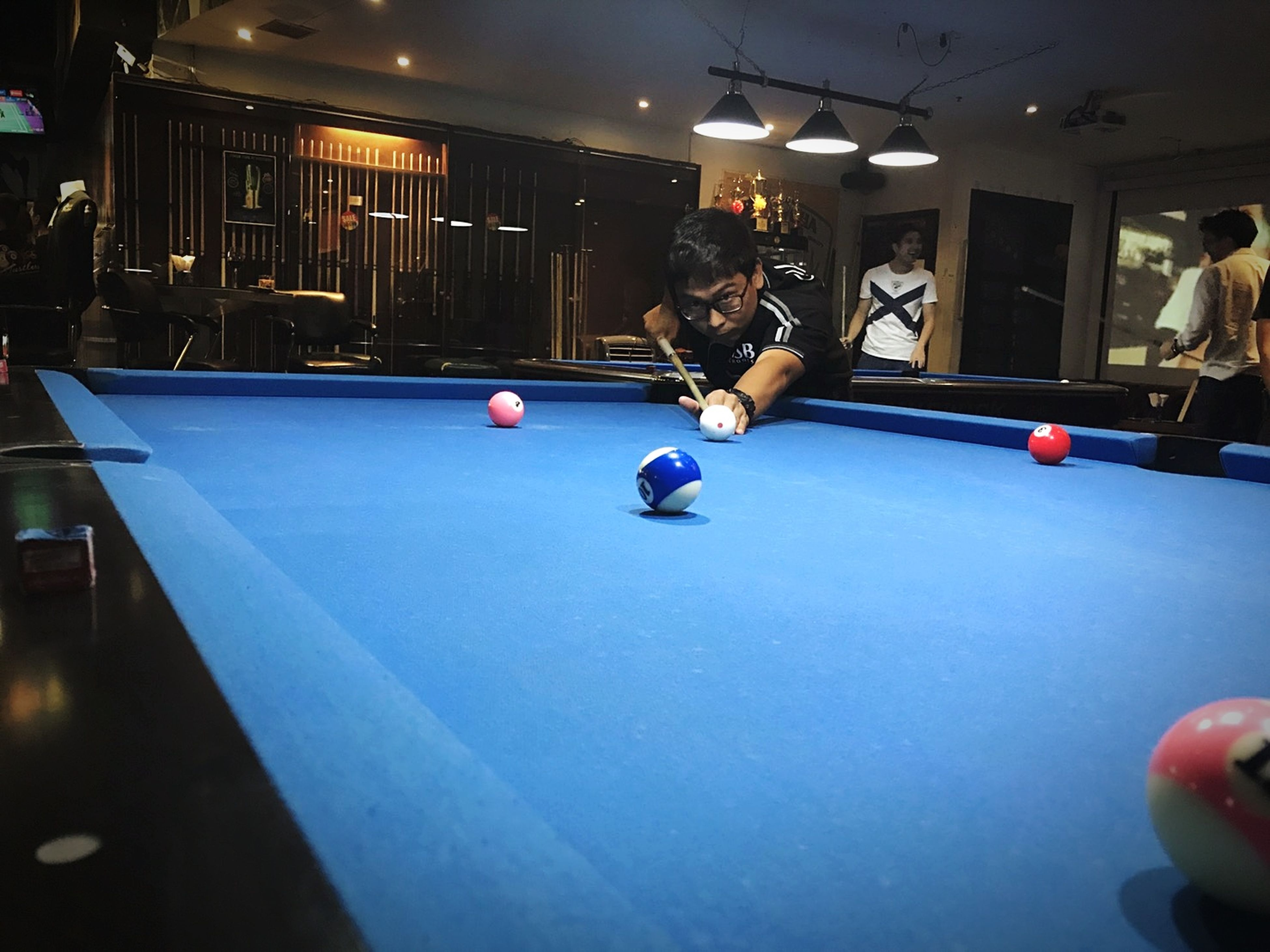 pool ball, pool table, pool - cue sport, sport, pool cue, playing, ball, snooker, lifestyles, leisure games, leisure activity, real people, indoors, recreational pursuit, snooker ball, blue, pool hall, competition, concentration, cue ball, one person, snooker and pool, human hand, friendship, young adult, people