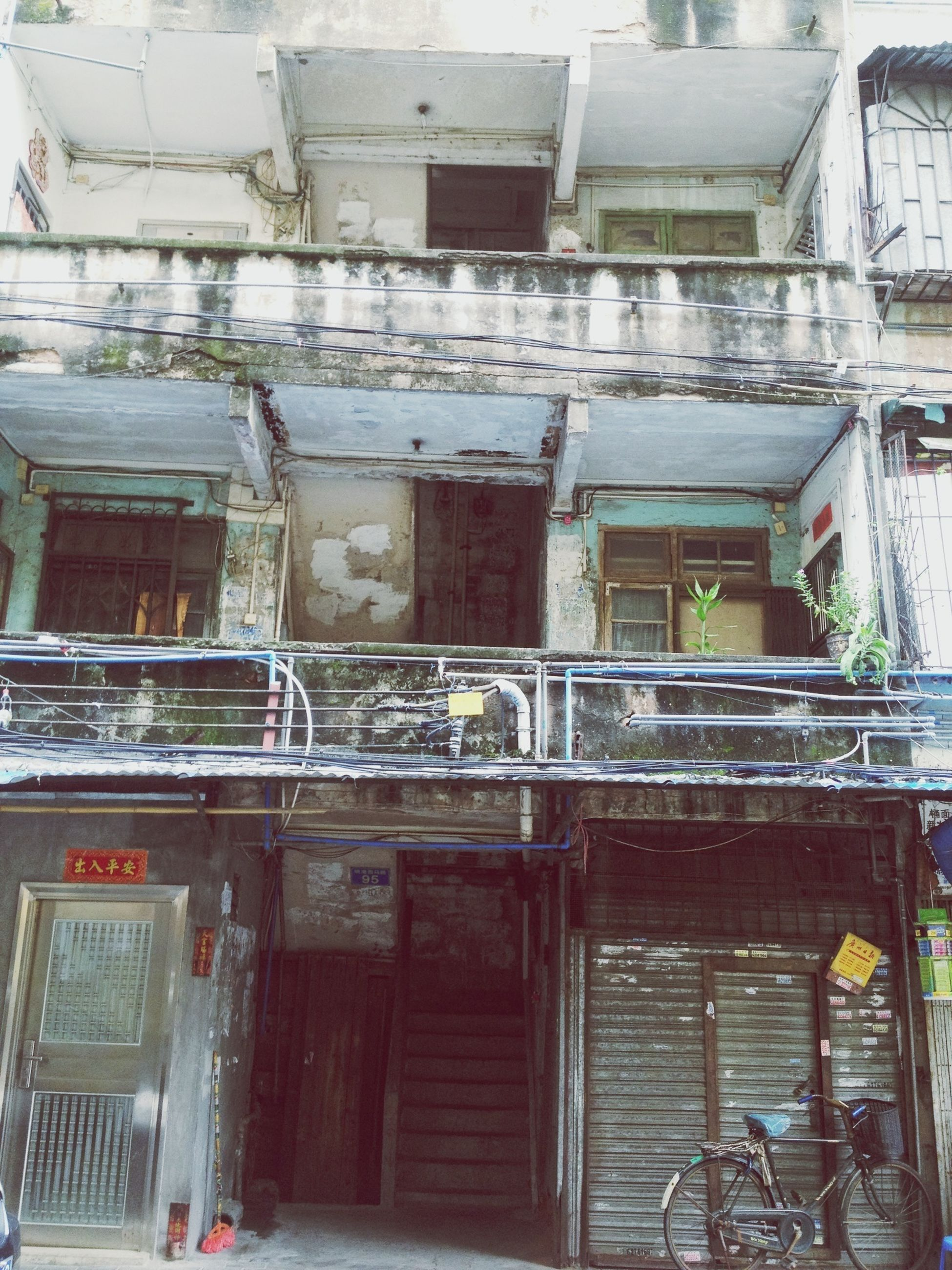 building exterior, architecture, built structure, window, residential structure, residential building, house, building, men, day, bicycle, outdoors, transportation, old, door, street, city, balcony