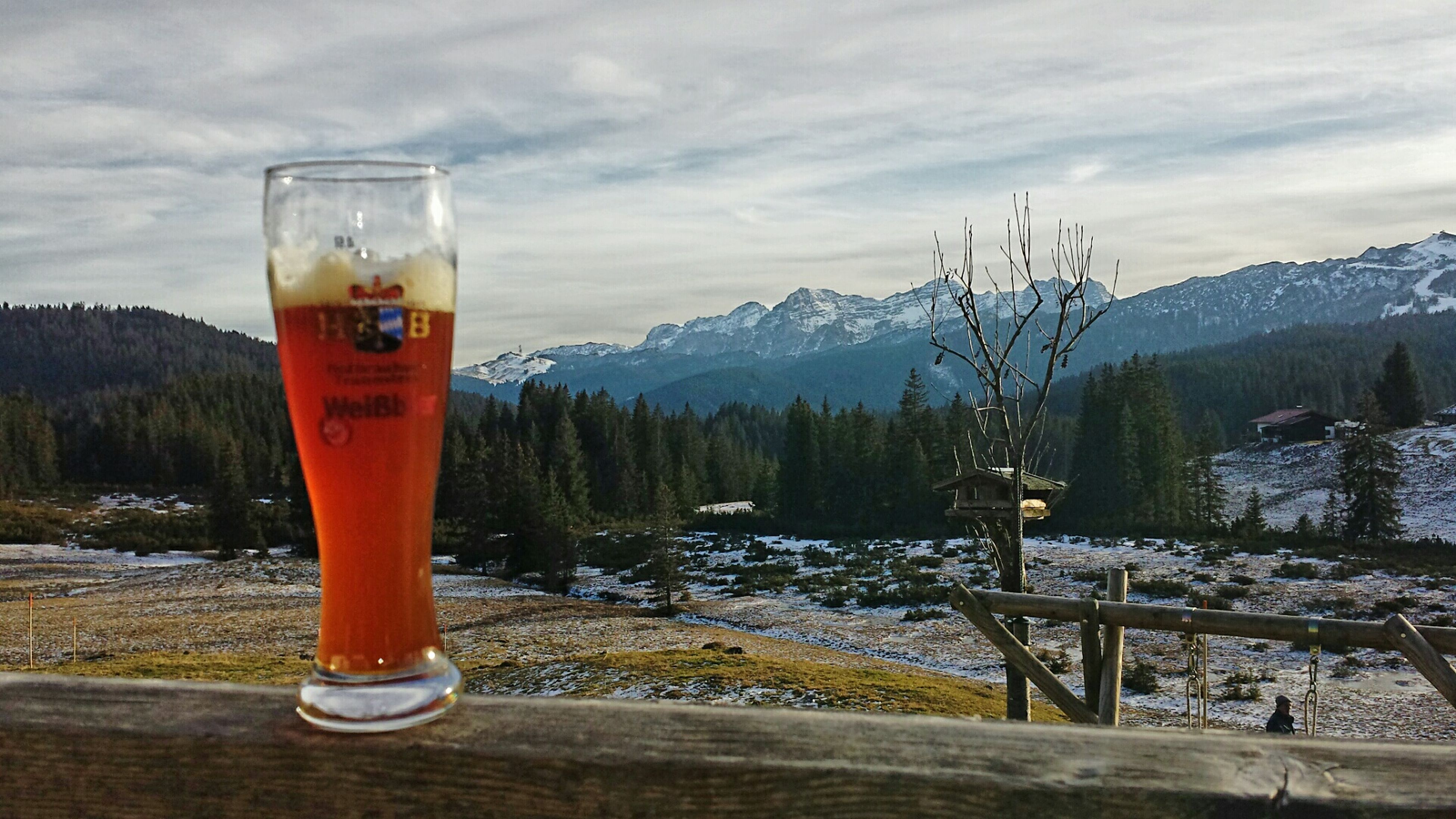 drink, food and drink, cold temperature, mountain, refreshment, sky, drinking glass, table, mountain range, water, tranquil scene, scenics, alcohol, cloud - sky, ice, tranquility, text, landscape, day, winter