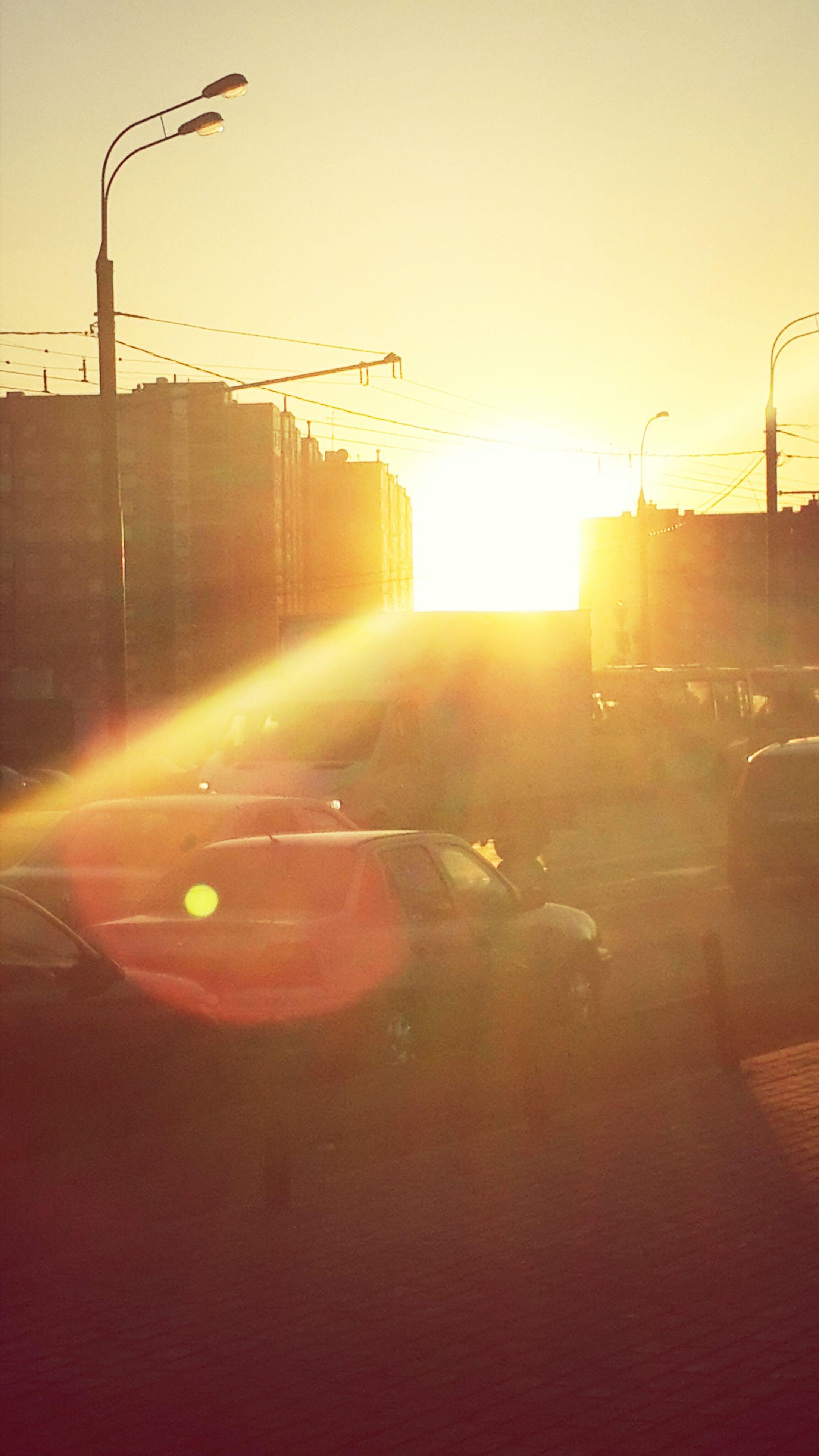 sunset, transportation, sun, street light, road, mode of transport, sunlight, car, lens flare, land vehicle, sunbeam, clear sky, street, silhouette, sky, electricity pylon, outdoors, no people, orange color, built structure