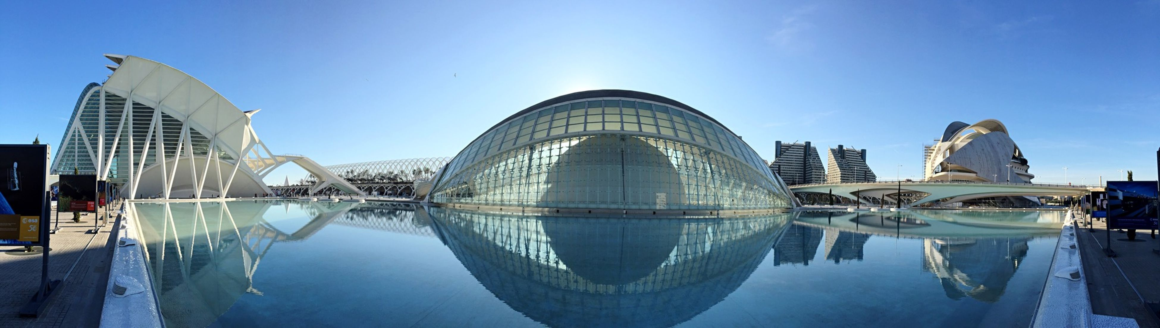 architecture, built structure, building exterior, water, reflection, blue, city, modern, clear sky, waterfront, sky, famous place, capital cities, river, travel destinations, panoramic, day, sunlight, fountain, outdoors
