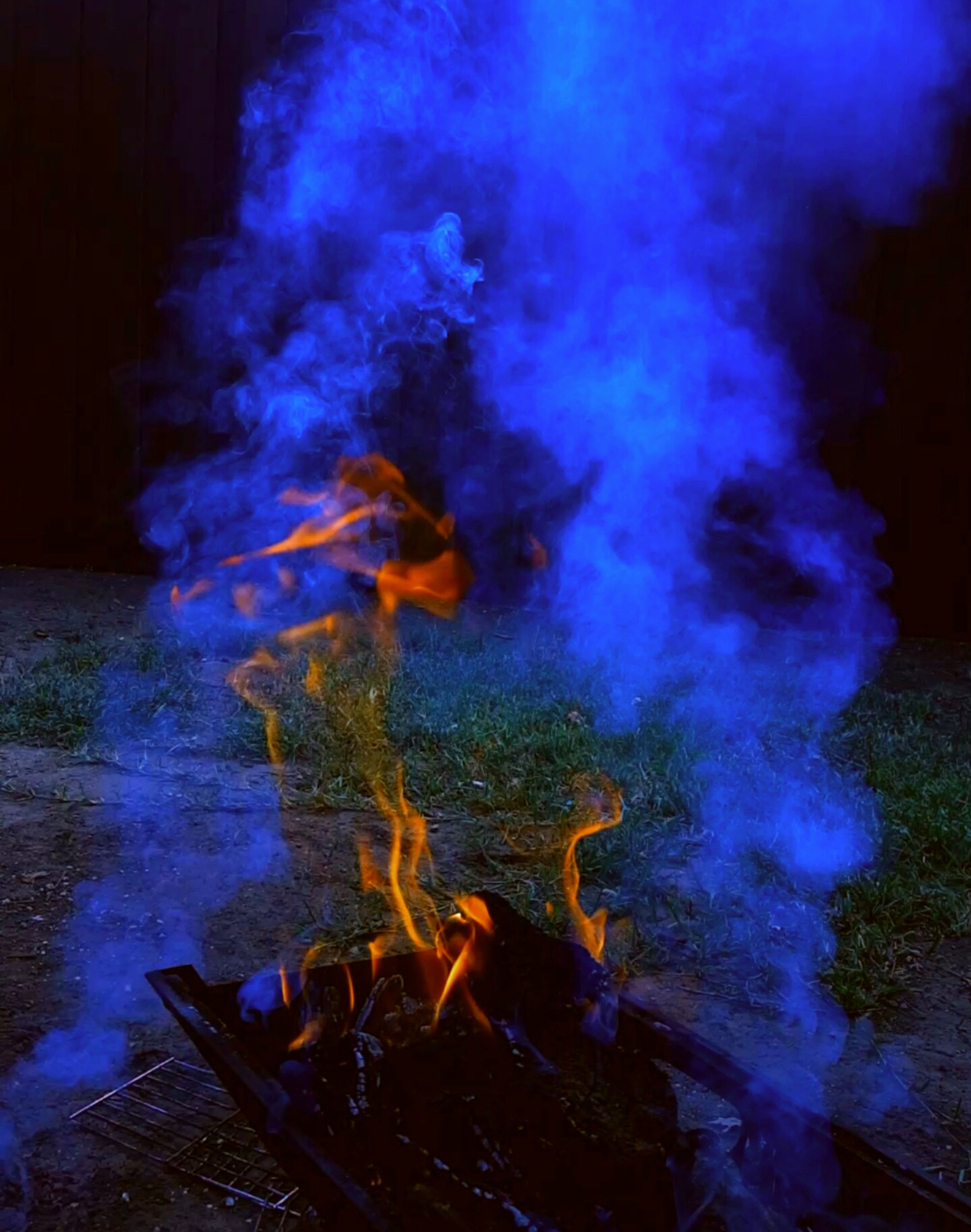 fire - natural phenomenon, burning, night, flame, heat - temperature, illuminated, long exposure, glowing, smoke - physical structure, motion, bonfire, light - natural phenomenon, smoke, campfire, arts culture and entertainment, fire, sparks, danger, blurred motion, indoors