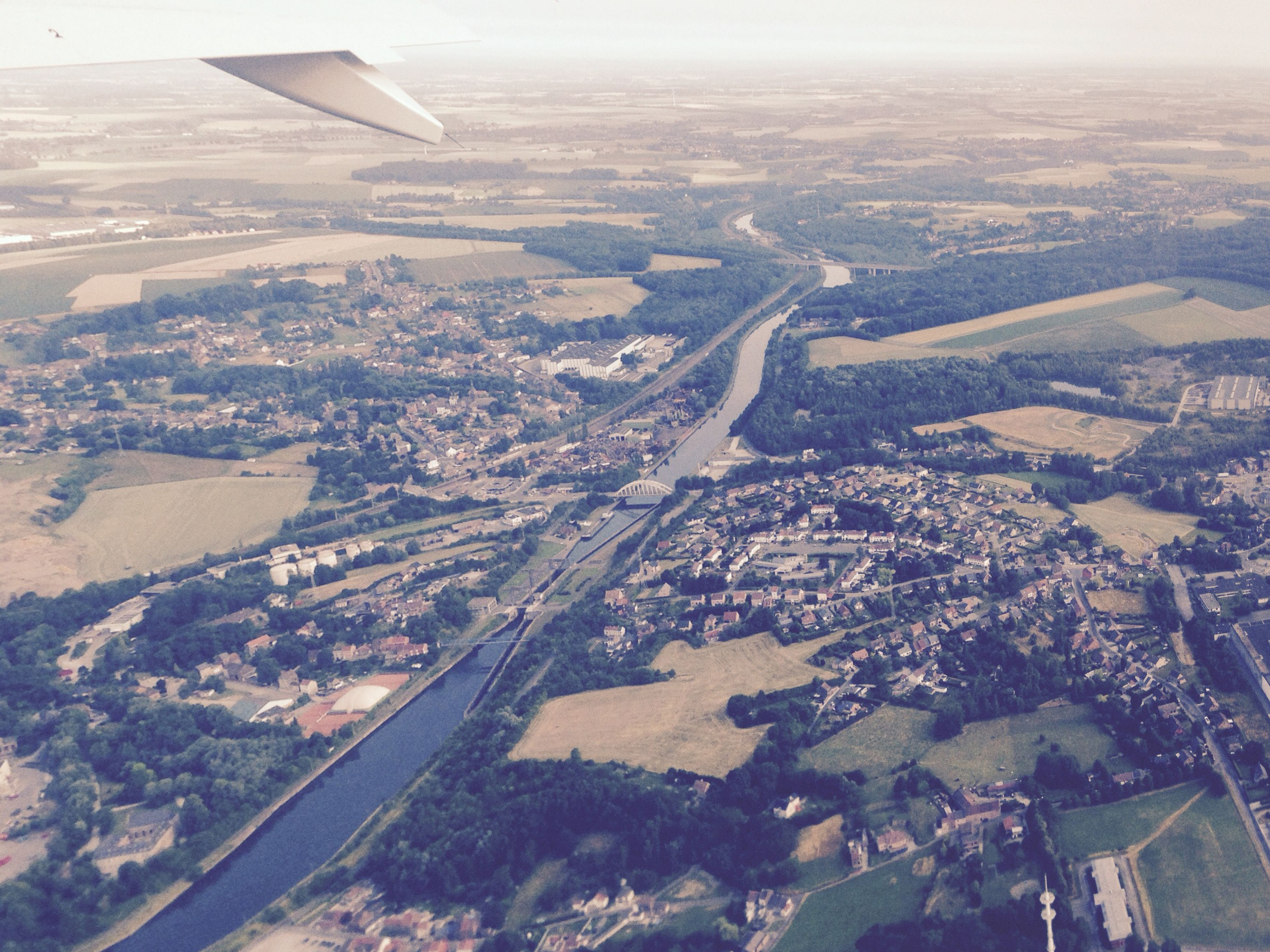 flying, aerial view, airplane, air vehicle, transportation, landscape, aircraft wing, mode of transport, mid-air, part of, cropped, high angle view, scenics, horizon over land, travel, nature, cityscape, on the move, sky, day