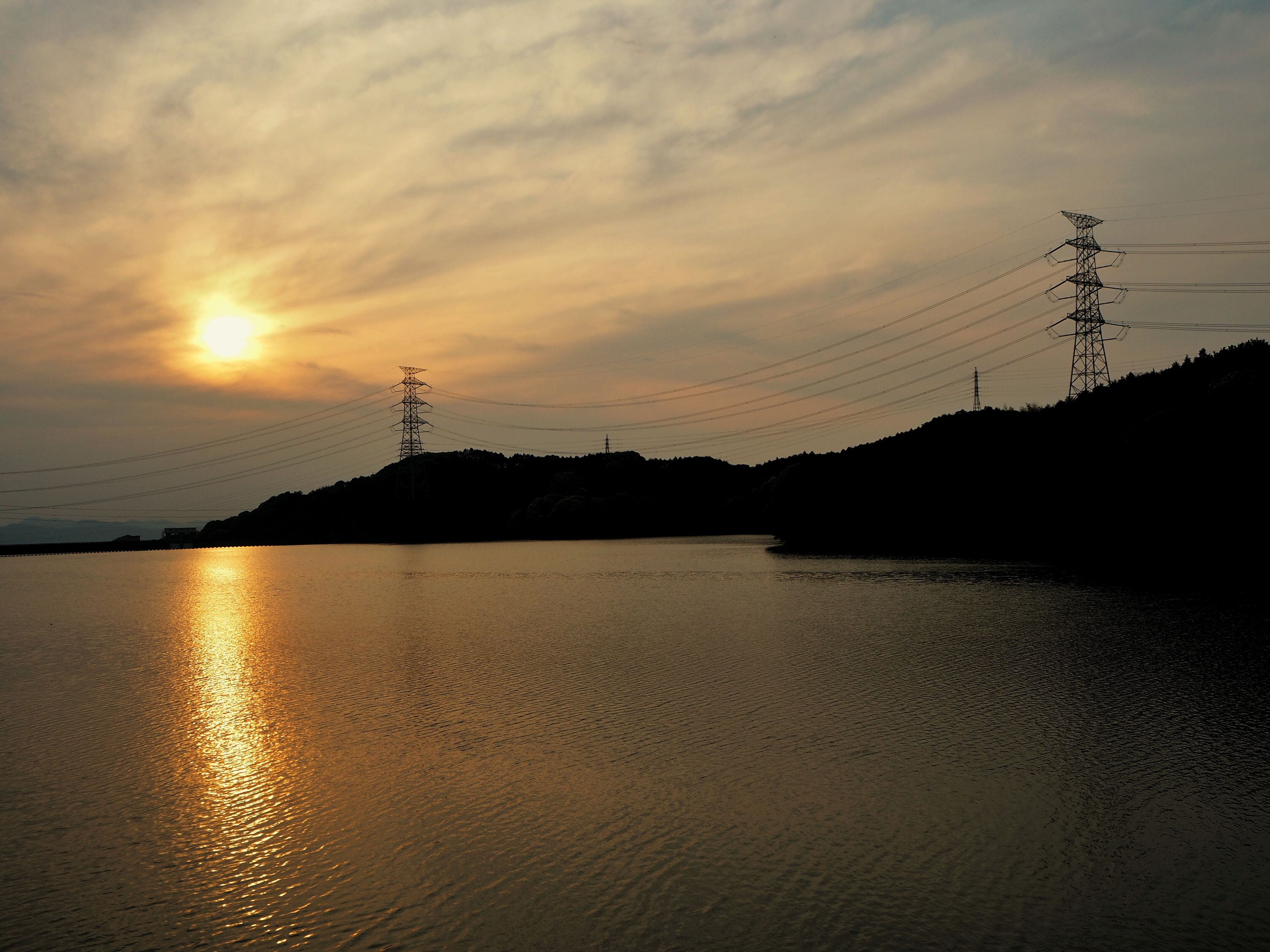 sunset, water, silhouette, sun, reflection, sky, tranquil scene, scenics, tranquility, beauty in nature, orange color, electricity pylon, idyllic, nature, power line, cloud - sky, waterfront, sunlight, lake, cloud