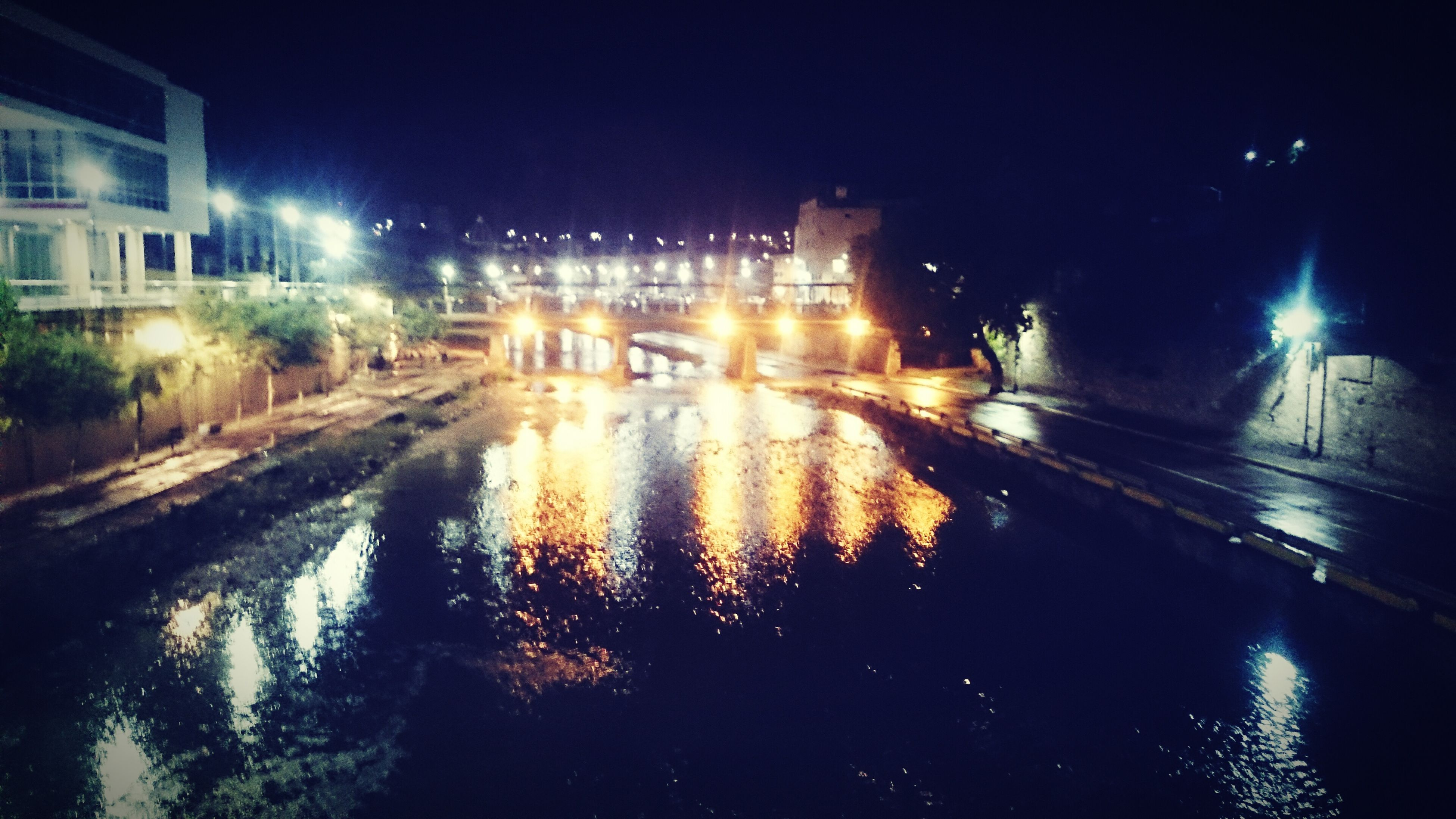 night, illuminated, water, building exterior, architecture, built structure, reflection, street light, street, city, wet, transportation, waterfront, puddle, road, lighting equipment, canal, outdoors, sky, rain
