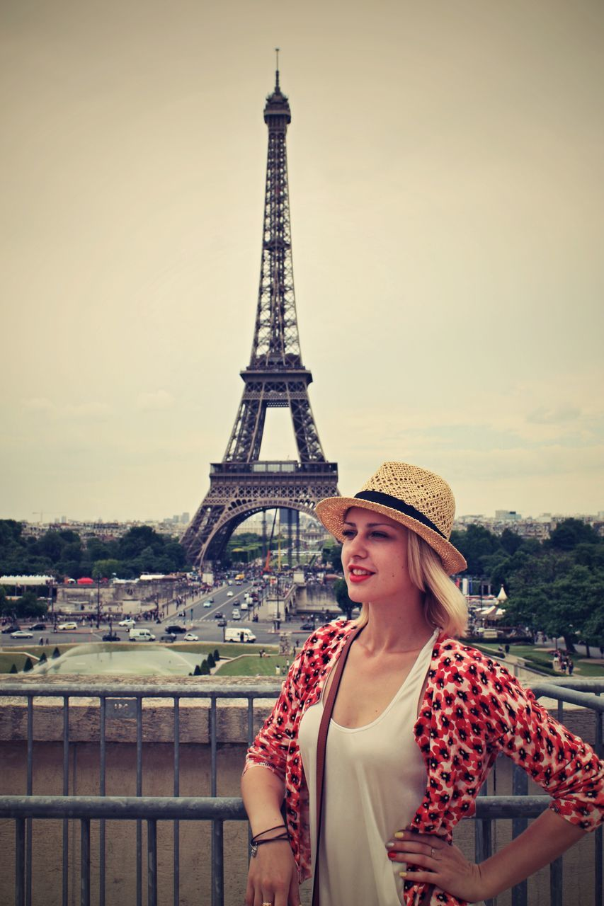 Beautiful Woman With Hand On Hip Standing By Eiffel Tower Against Clear Sky
