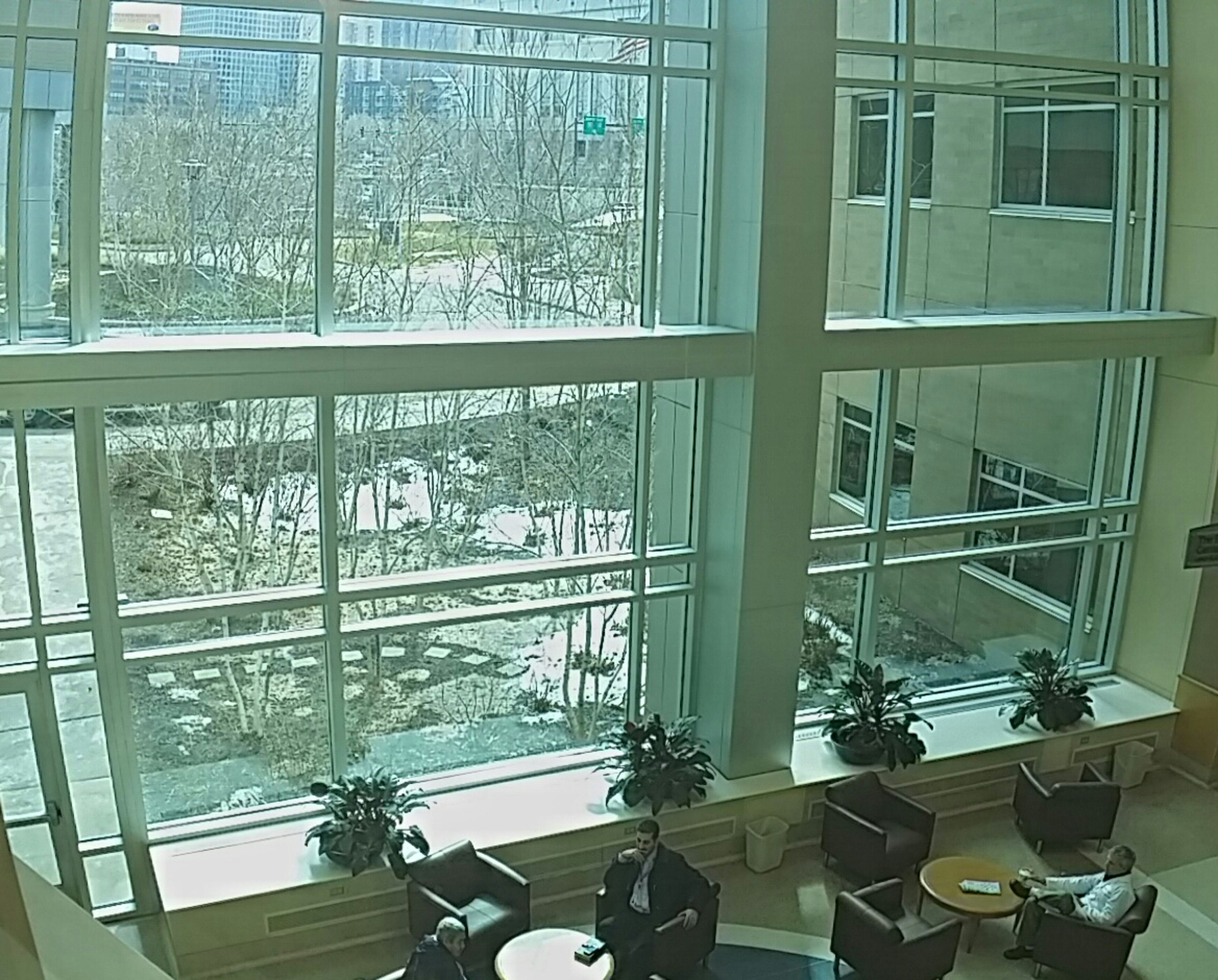 window, indoors, architecture, built structure, glass - material, building exterior, building, day, transparent, reflection, modern, no people, city, interior, railing, balcony, low angle view, wall, chair, communication