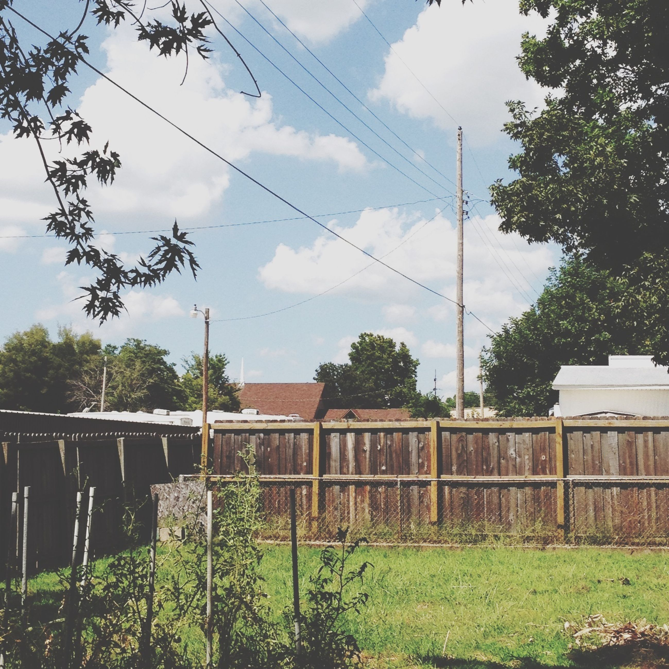 sky, architecture, built structure, building exterior, cloud - sky, tree, fence, cloud, house, grass, plant, growth, field, day, power line, cloudy, outdoors, no people, old, green color
