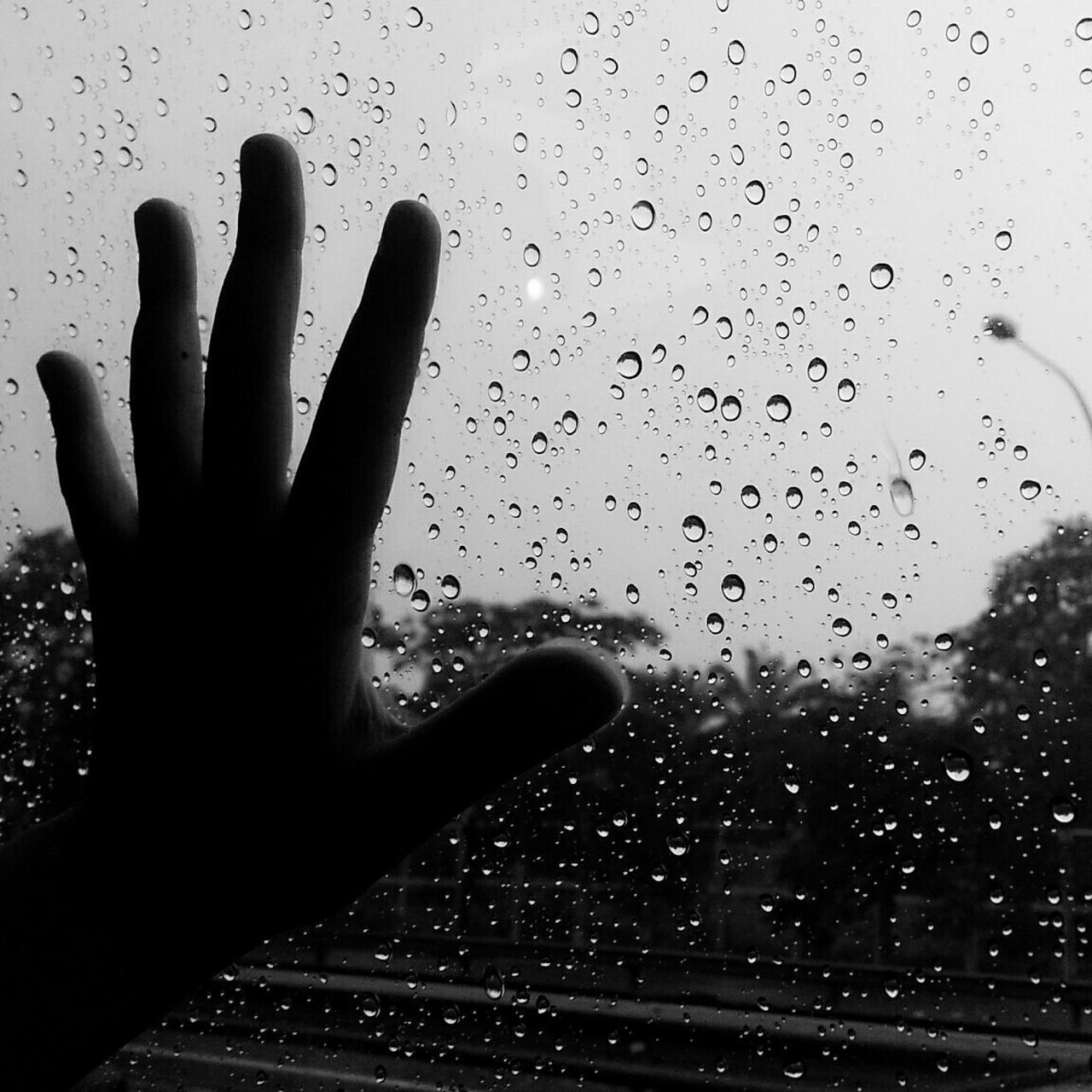 Cropped Image Of Boy Touching Wet Window During Monsoon