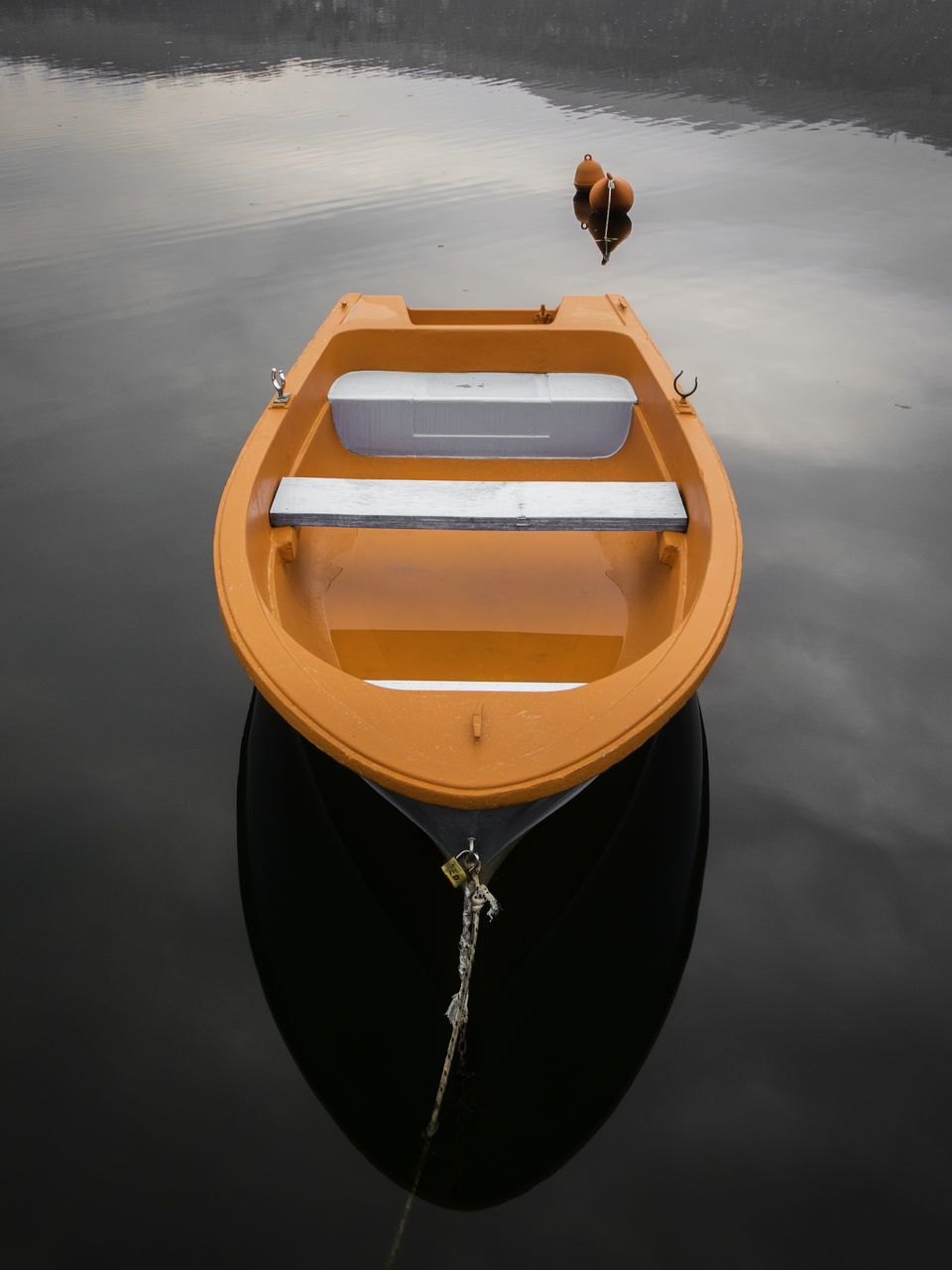 High Angle View Of Orange Rowboat Moored In Calm Lake