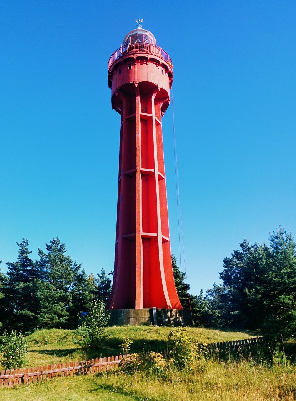 tree, lighthouse, day, clear sky, blue, tower, low angle view, grass, red, no people, architecture, outdoors, protection, guidance, growth, built structure, nature, beauty in nature, water tower - storage tank, sky