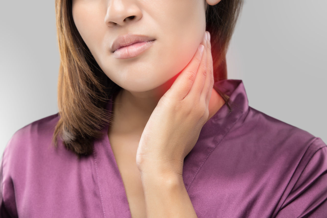 Woman with a sore throat holding her neck Cancer Close-up Front View Gland Lump Lymph Lymphadenitis Lymphadenopathy Neck Nodes One Person Palpation Pink Color Real People SORE Studio Shot Swelling Swollen Throat Thyroid Upper White Background Women Young Adult Young Women