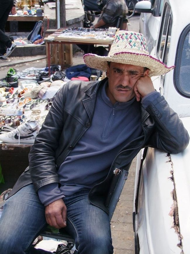 Moroccan Fed Up! Business Casual Clothing Composition Fed Up Fes Front View Hat Lifestyles Looking At Camera Man Market Stall Market Trader Moroccan Morocco Occupation Portrait Real People Sitting Three Quarter Length Traditional Unhappy