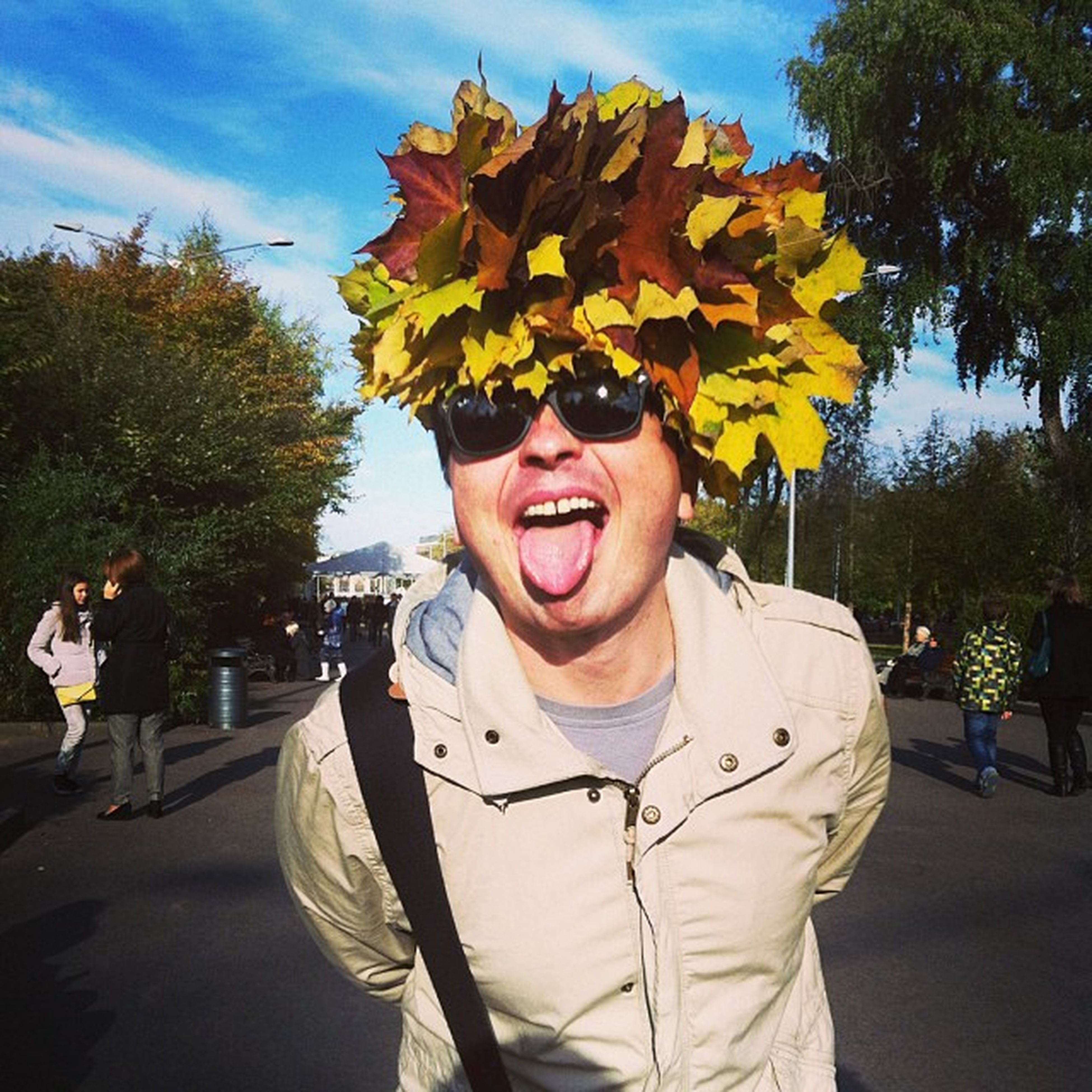 lifestyles, person, leisure activity, casual clothing, tree, front view, looking at camera, portrait, young adult, standing, smiling, holding, sunglasses, happiness, park - man made space, yellow, waist up, flower