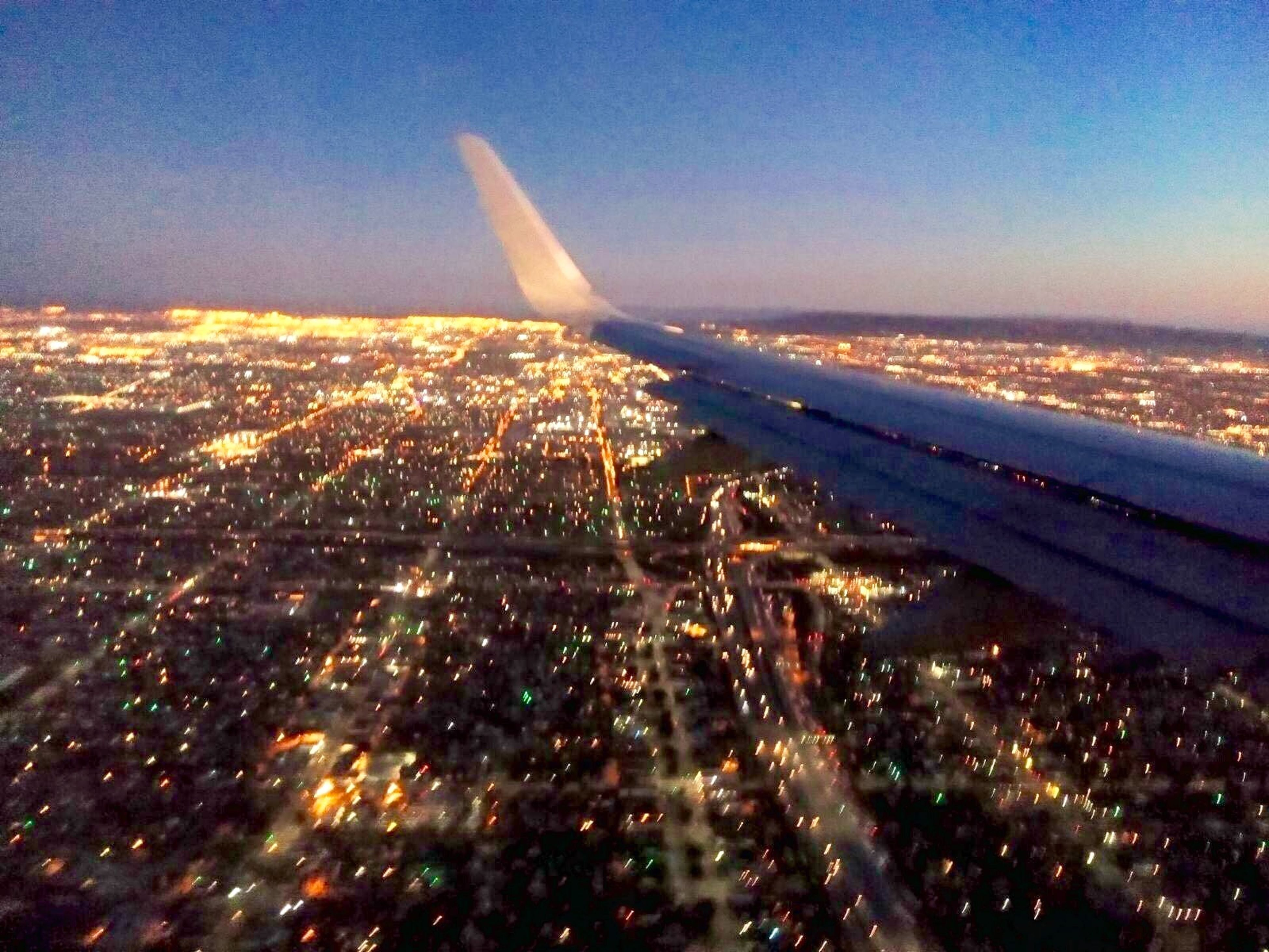 city, cityscape, aerial view, illuminated, transportation, architecture, night, built structure, travel, airplane, mode of transport, clear sky, air vehicle, building exterior, crowded, flying, on the move, sky, capital cities, high angle view