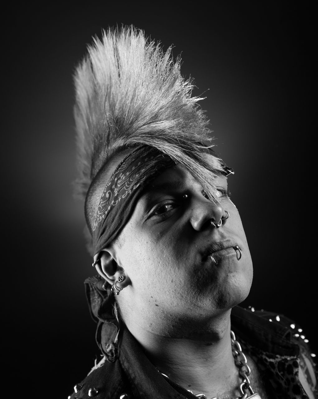 Portrait Of Man With Spiky Hair Against Black Background