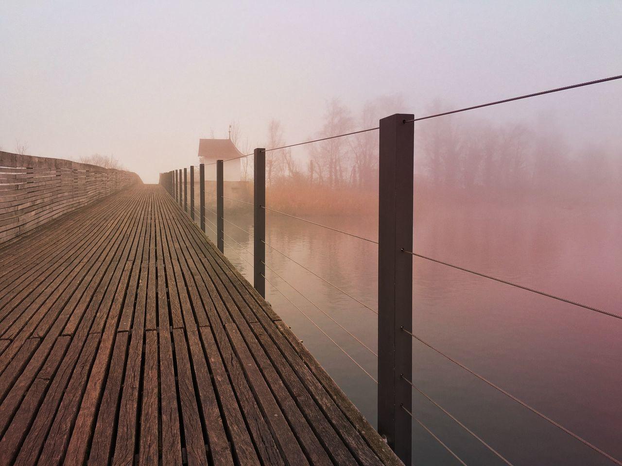 Boardwalk By Lake In Foggy Weather