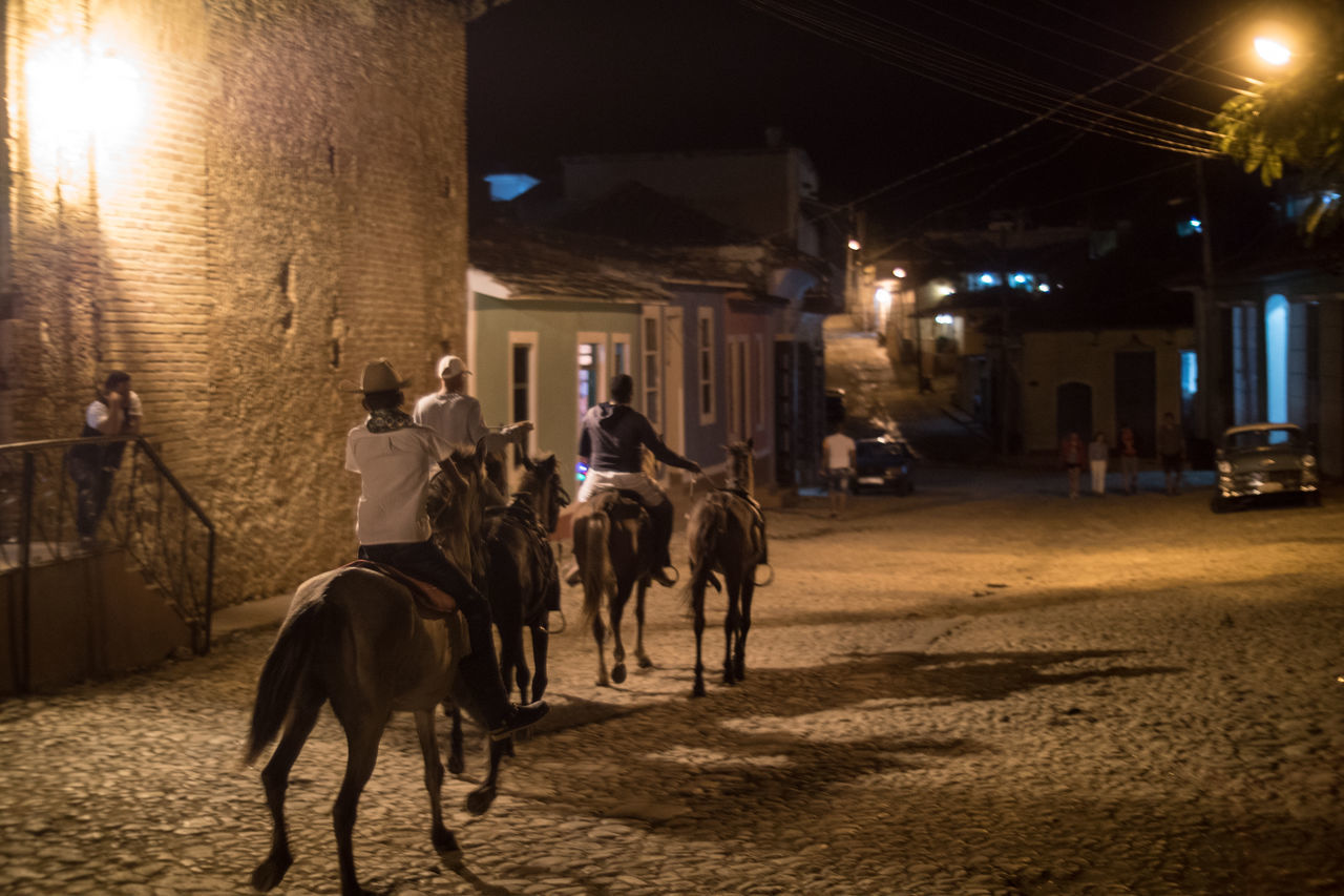 Coming home from work on Saturday Adult Animal Themes City Cuba Cuba Collection Domestic Animals Horse Horseback Riding Mammal Night Outdoors People Rear View Riding UNESCO World Heritage Site Working Animal