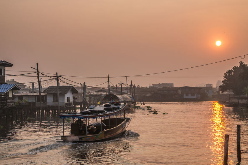 village near river in morning with early morning sky with sun at in Thailand Architecture Beauty In Nature Boat City Idyllic Mode Of Transport Nature Nautical Vessel Orange Color Outdoors River Sky Sun Sunset Tranquil Scene Tranquility Water