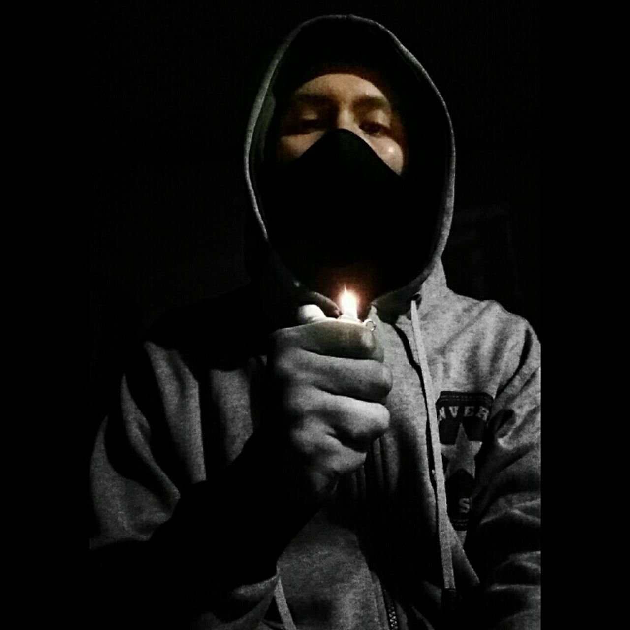 hood - clothing, front view, hooded shirt, real people, flame, one person, black background, indoors, illuminated, studio shot, night, close-up, young adult, people
