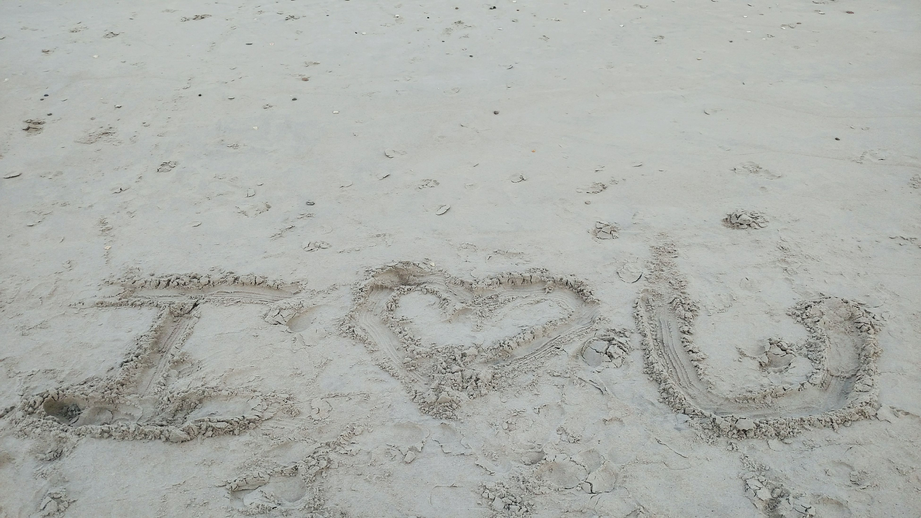 full frame, backgrounds, sand, textured, text, western script, close-up, footprint, beach, pattern, communication, no people, day, outdoors, high angle view, ideas, wet, heart shape, creativity, wall - building feature