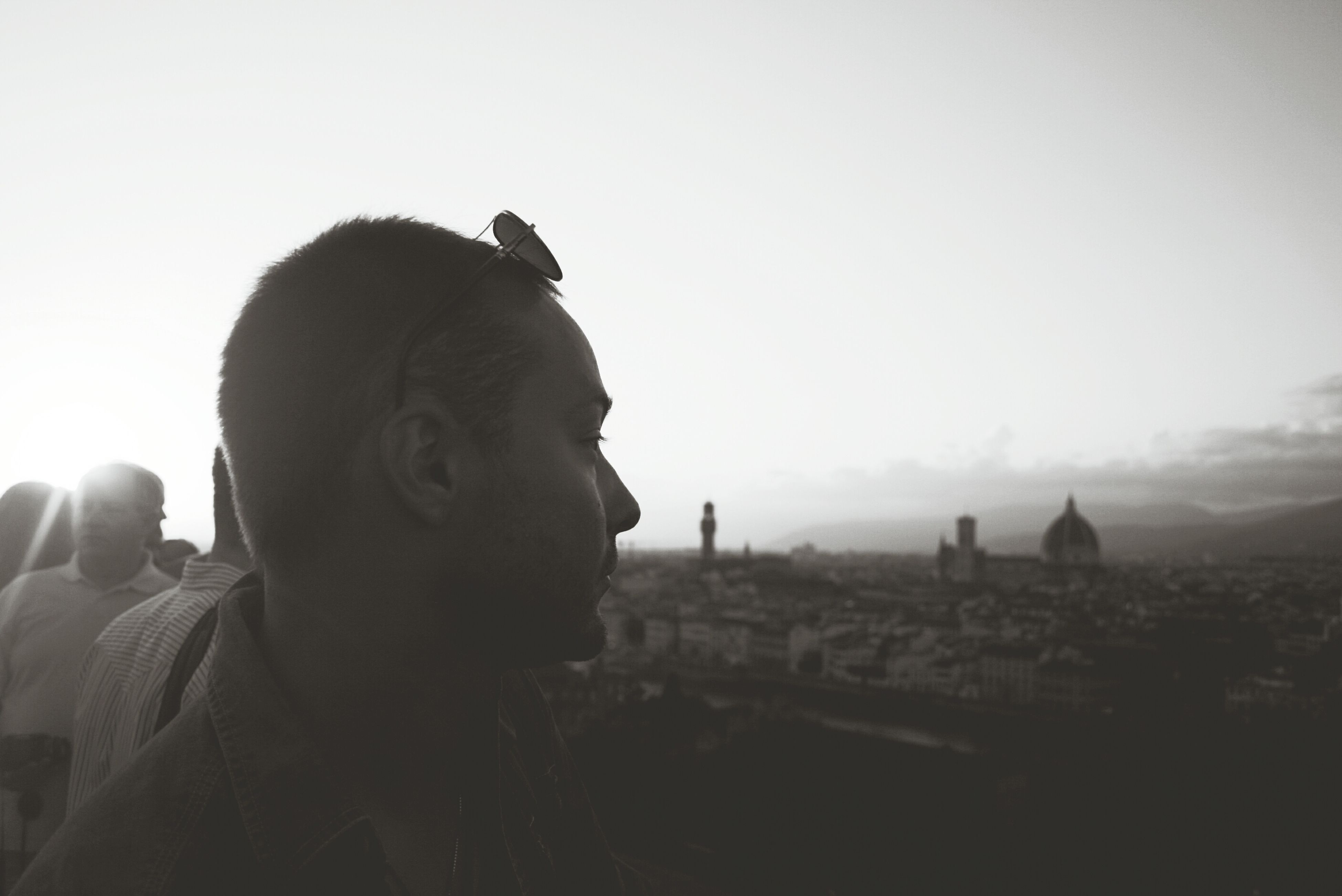 clear sky, copy space, lifestyles, headshot, leisure activity, one animal, men, animal themes, mammal, looking away, sitting, standing, young men, contemplation, silhouette, waist up, sky, rear view
