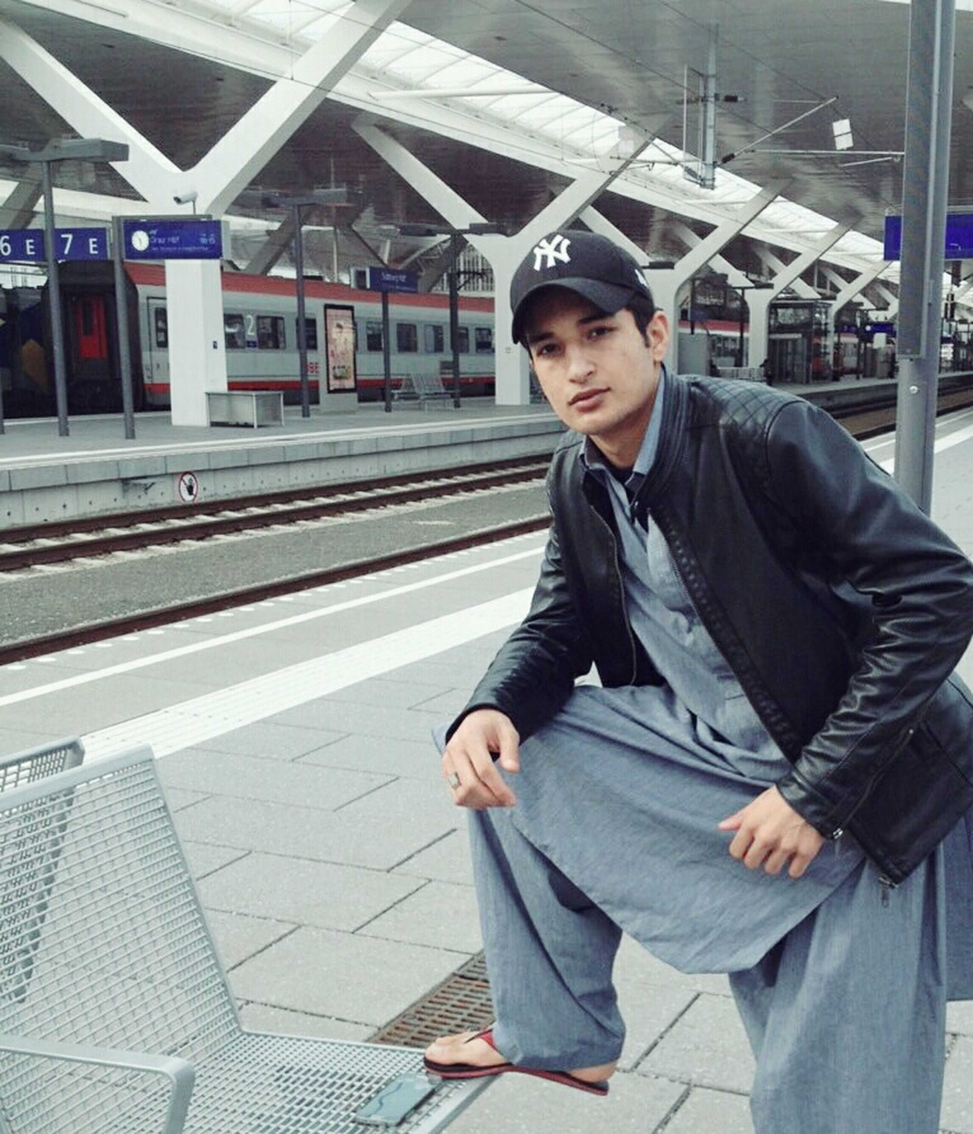 young adult, casual clothing, lifestyles, person, transportation, portrait, looking at camera, young men, front view, leisure activity, standing, sitting, three quarter length, mode of transport, smiling, public transportation, railroad station platform
