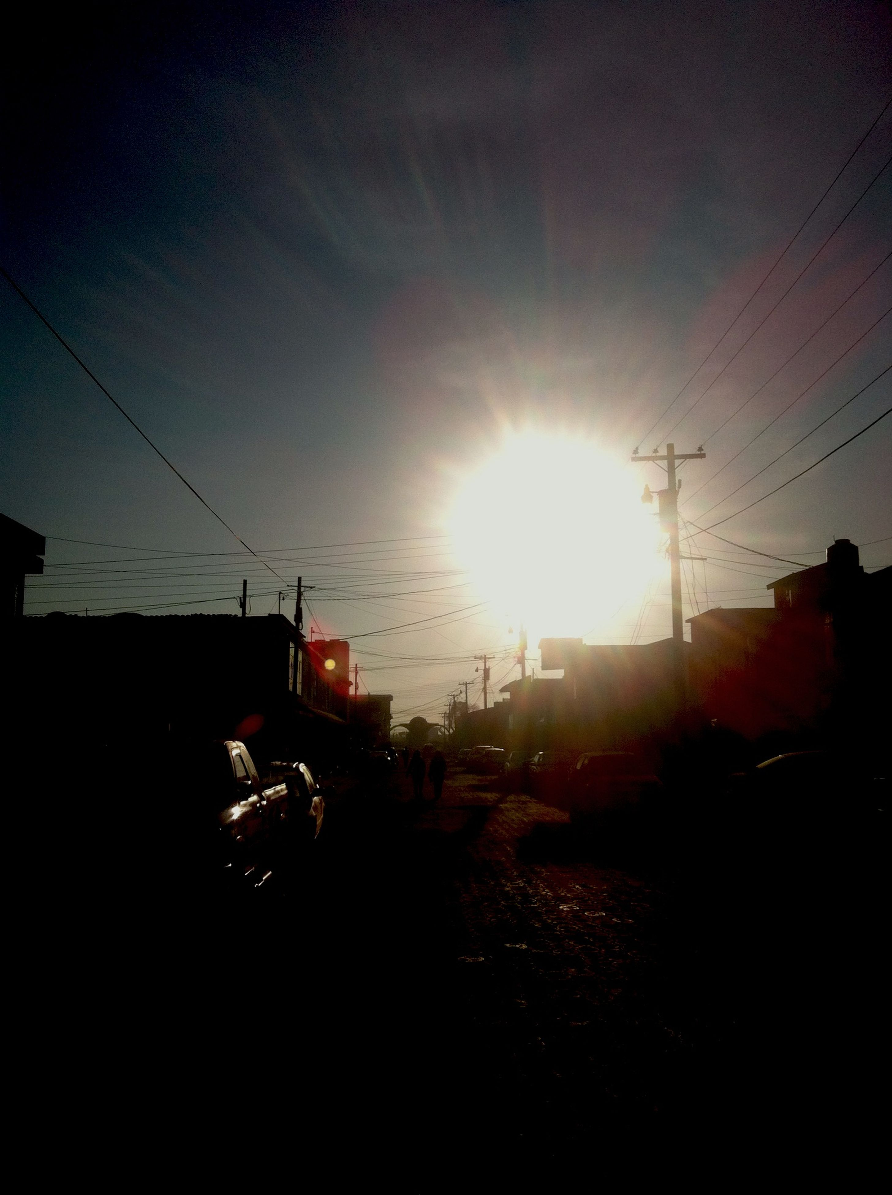 power line, electricity pylon, sun, building exterior, power supply, electricity, cable, sunlight, built structure, transportation, architecture, sunbeam, silhouette, sky, sunset, house, lens flare, power cable, mode of transport, fuel and power generation