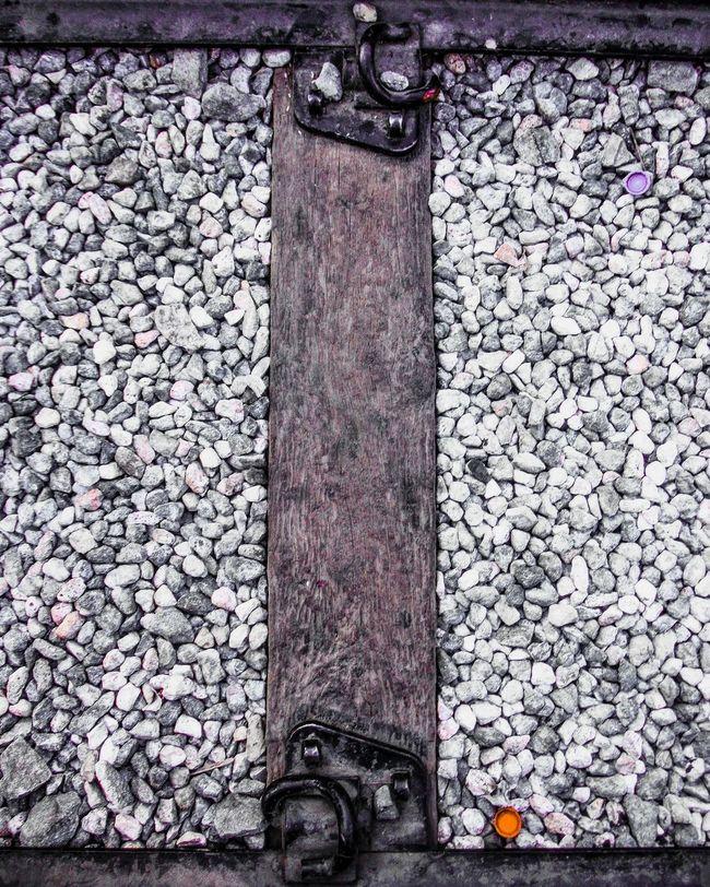 A spot of color in a sea of white and grey Bottle Caps Gravel Train Tracks White Rocks Traintracks Bottle Cap Bottlecaps Touch Of Color Spot Of Color White And Grey Greyscale Carmine Filter Wood - Material Wood Wooden Train Track Metal Metal Tracks Kanchanaburi River Kwai Bridge Thailand EyeEm Thailand Traveling Thailand Fujifilm Finepix Xp60