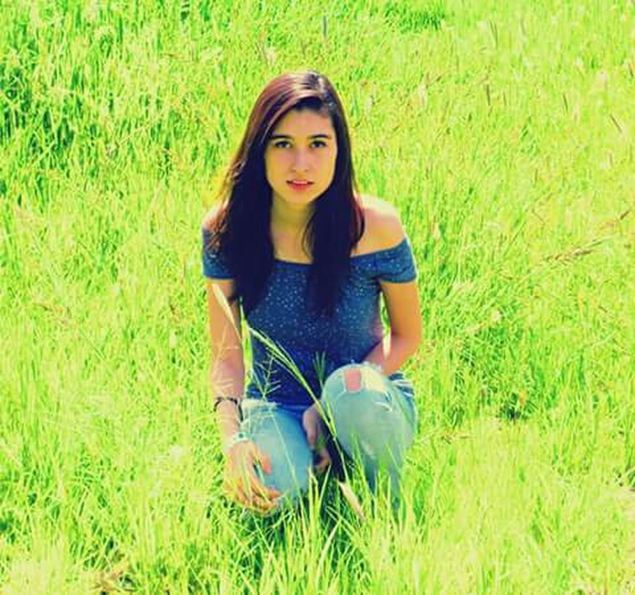 grass, looking at camera, one person, portrait, front view, casual clothing, beautiful woman, green color, growth, long hair, outdoors, standing, young adult, day, nature, beauty, leisure activity, only women, people, one young woman only, real people, adults only, one woman only, beautiful people, adult, young women, beauty in nature, flower, freshness