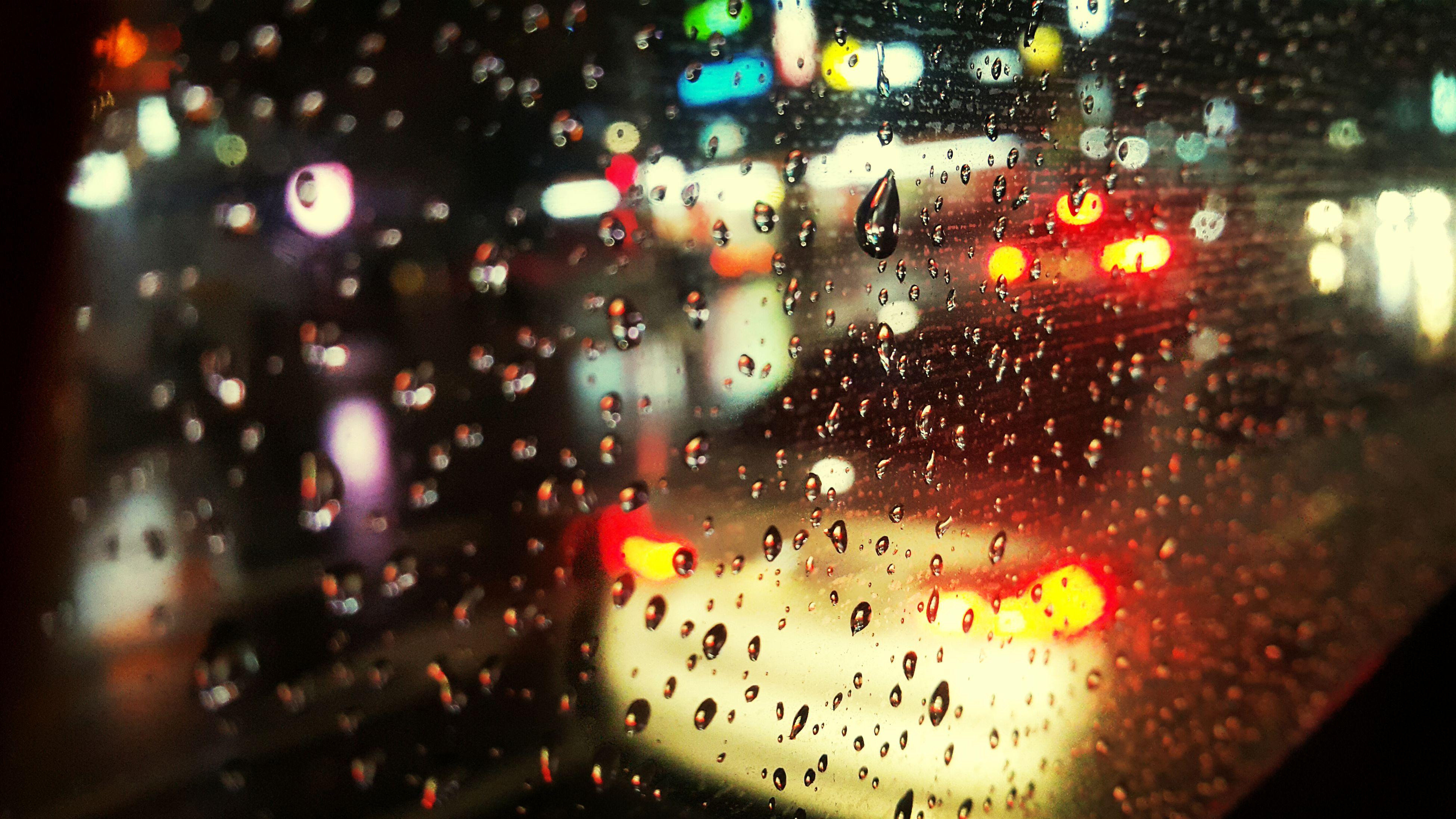 illuminated, night, car, wet, city, window, indoors, land vehicle, rain, street, transportation, city street, architecture, transparent, glass - material, drop, road, building exterior, traffic, mode of transport