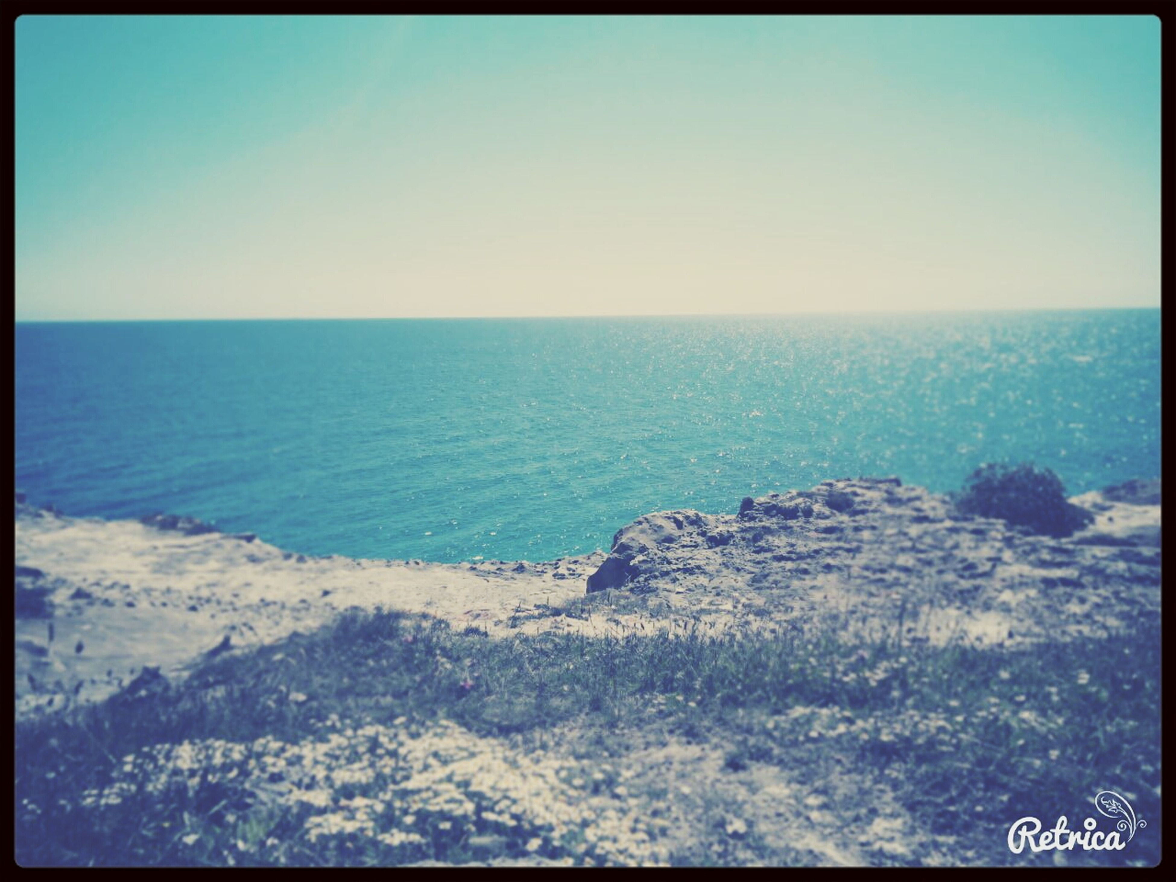 sea, transfer print, horizon over water, water, scenics, tranquil scene, auto post production filter, tranquility, beauty in nature, clear sky, nature, blue, beach, shore, sky, coastline, copy space, idyllic, rock - object, day