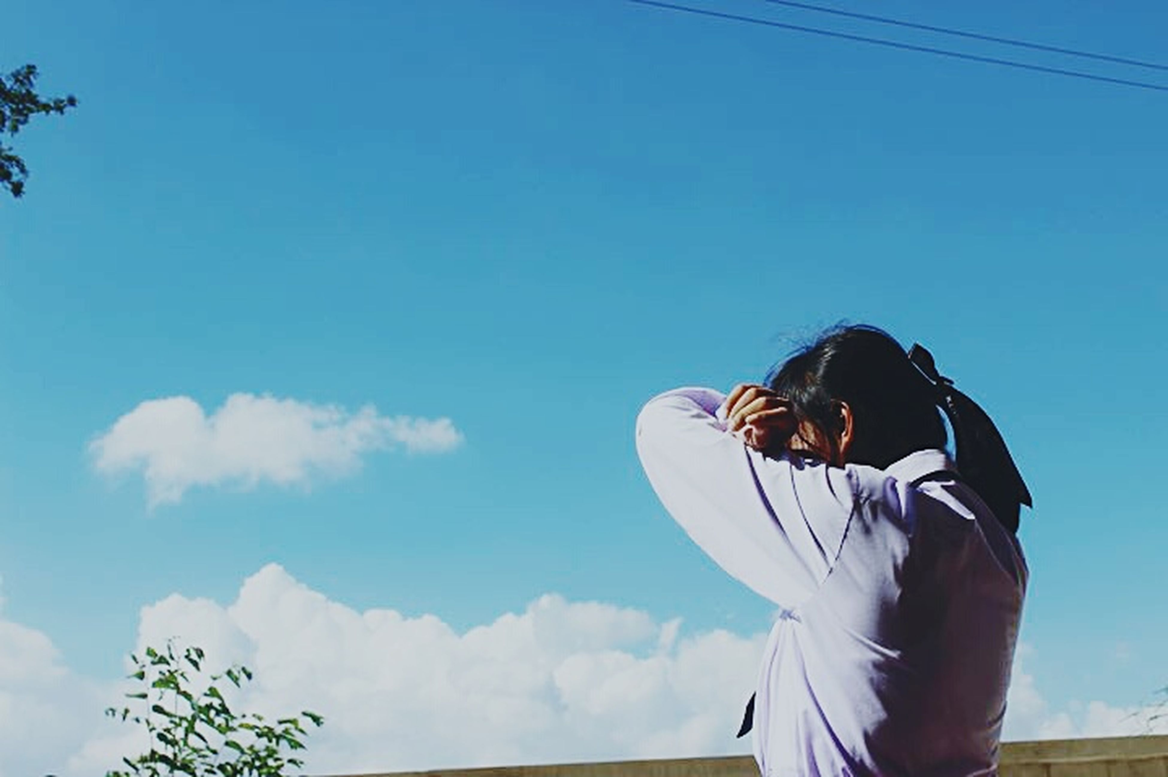 lifestyles, leisure activity, young adult, blue, clear sky, low angle view, casual clothing, sky, standing, young women, three quarter length, rear view, waist up, copy space, full length, long hair, holding, person