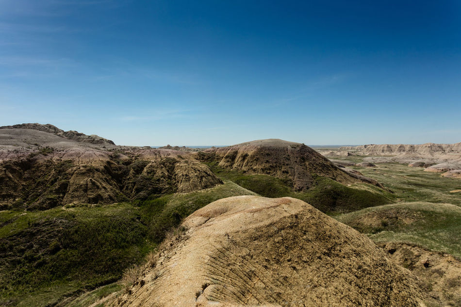 Badlands National Park Beauty In Nature Blue Calm Clear Sky Countryside Curve Day Footpath Green Landscape Mountain Narrow Nature Non-urban Scene Outdoors Remote Scenics Sky Solitude South Dakota South Dakota Badlands The Way Forward Tranquil Scene Tranquility
