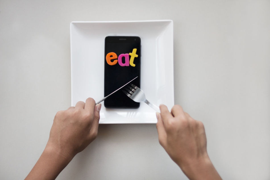 Smartphone with eat word on it in a white plate on a table. Alone Eating Internet Addiction Meal Mobile Phone Social Addiction Antisocial Cafe Conceptual Connection Eat Your Word Gadget Idiom Internet Online  Phone Plate Restaurant Smartphone Social Media Technology