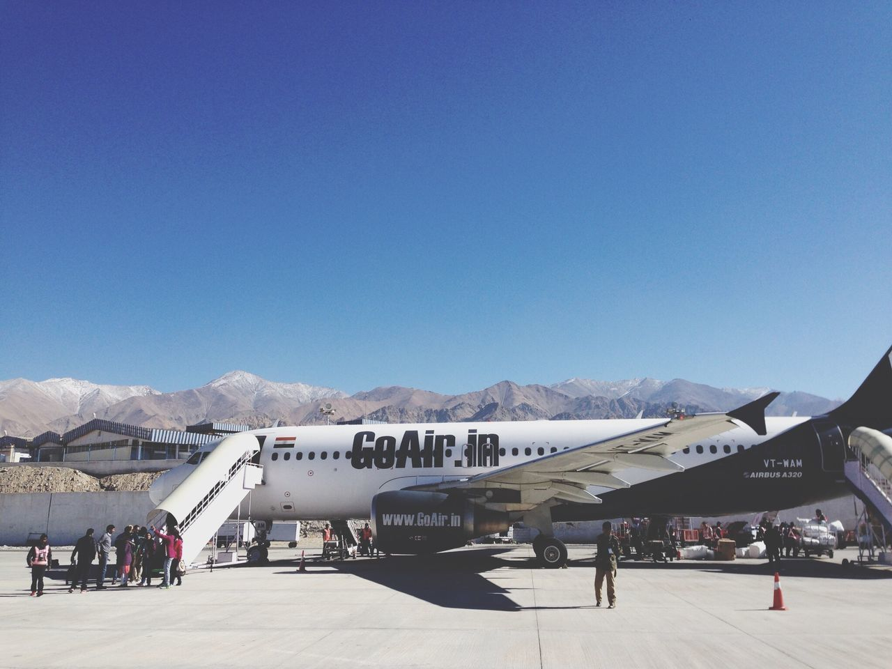 copy space, airport, day, transportation, airplane, mountain, clear sky, outdoors, blue, air vehicle, mountain range, large group of people, shadow, real people, sky, people