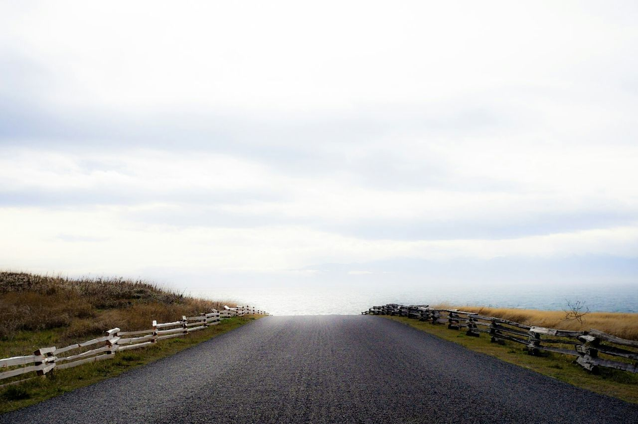 Road Amidst Fence Against Cloudy Sky