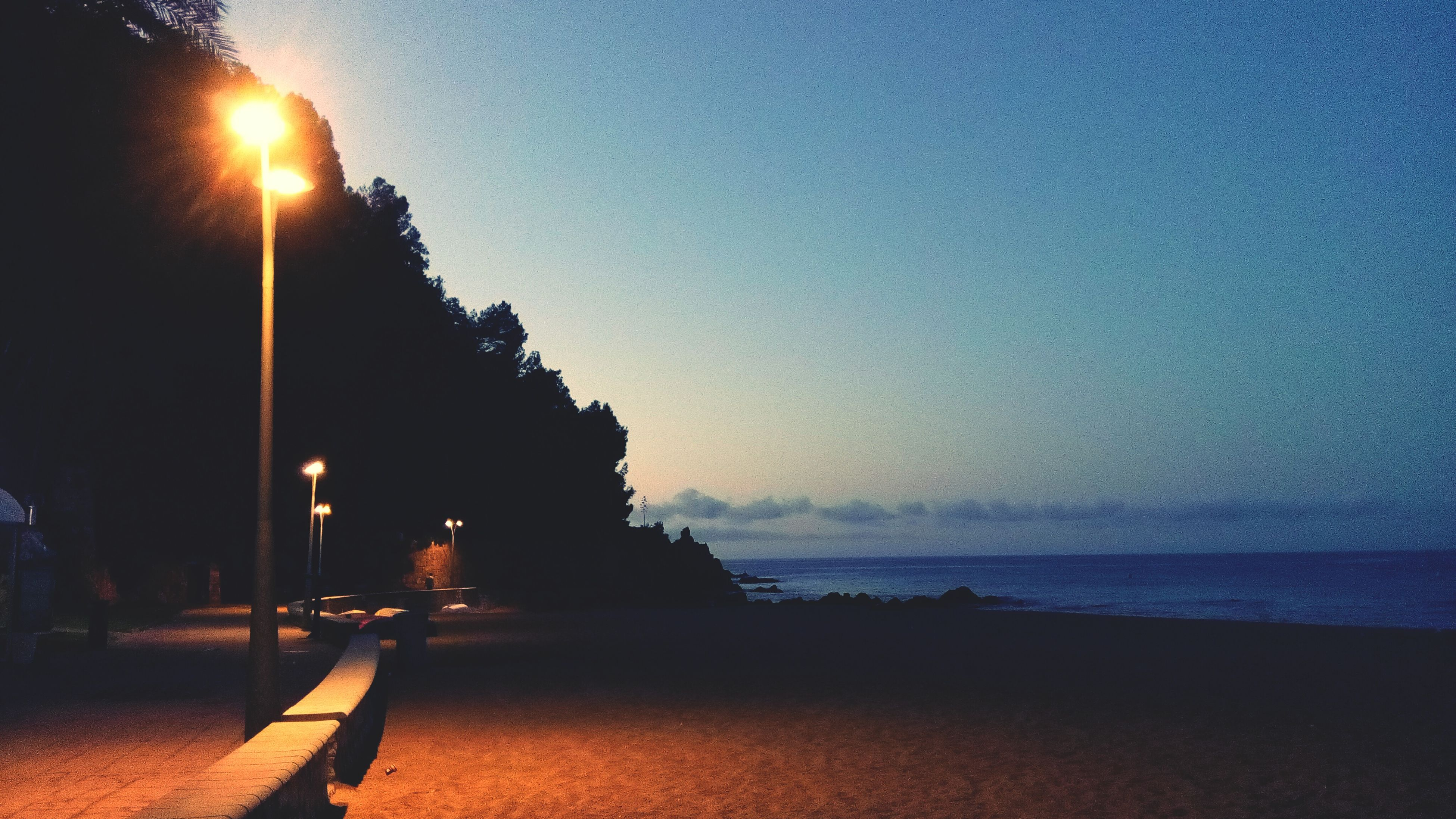sea, water, clear sky, sun, building exterior, sunset, built structure, sky, street light, illuminated, beach, copy space, architecture, horizon over water, sunlight, tranquility, tranquil scene, shore, nature, scenics