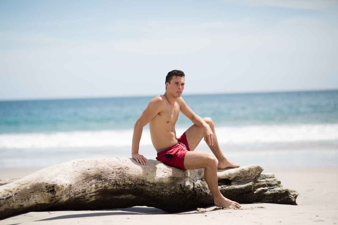 sea, shirtless, one person, water, real people, beach, rock - object, horizon over water, nature, full length, sky, day, beauty in nature, outdoors, young adult, men, young men, scenics, people