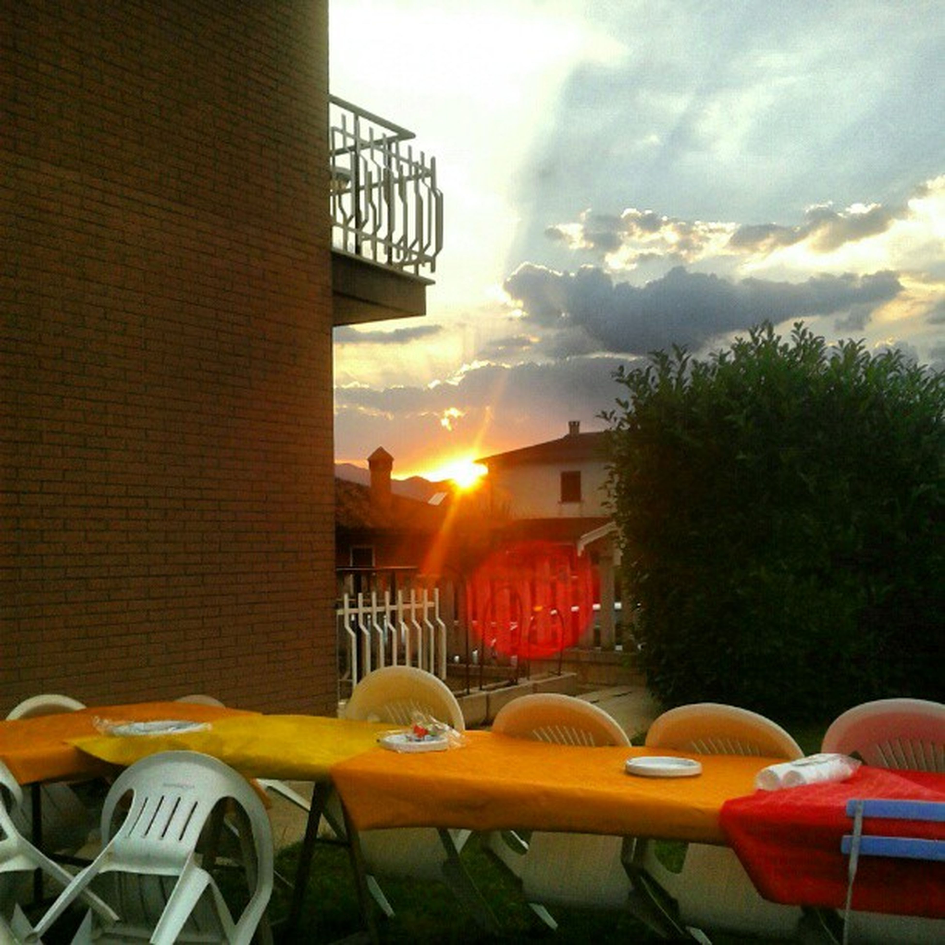 sunset, sky, architecture, built structure, building exterior, orange color, cloud - sky, sun, sunlight, chair, cloud, tree, house, nature, residential structure, outdoors, no people, railing, residential building, balcony
