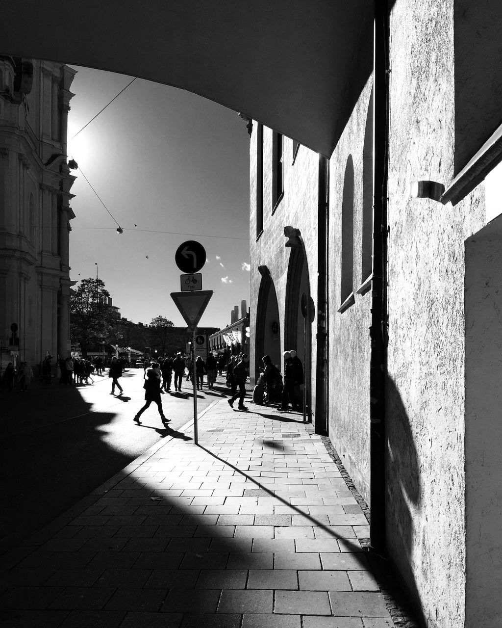 architecture, built structure, building exterior, sunlight, shadow, real people, architectural column, day, outdoors, men, lifestyles, women, city, sky, people