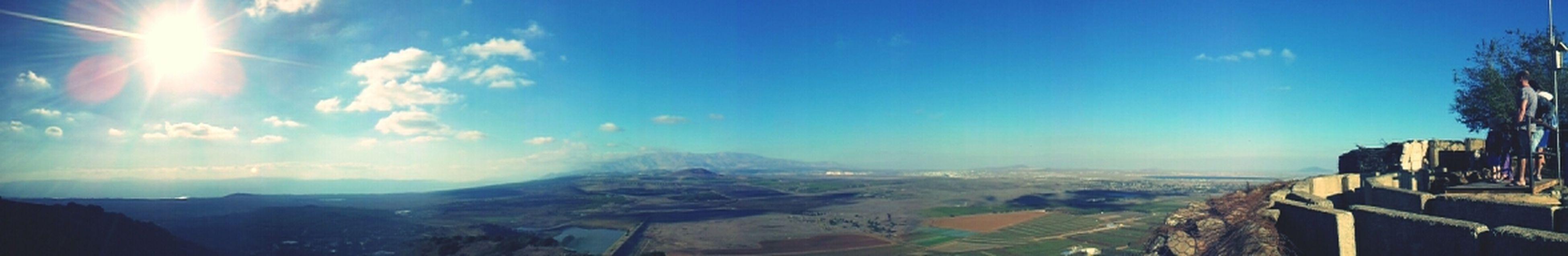 sky, mountain, blue, panoramic, scenics, tranquil scene, tranquility, sunlight, beauty in nature, landscape, nature, cloud - sky, sunbeam, mountain range, sun, cloud, built structure, building exterior, lens flare, architecture
