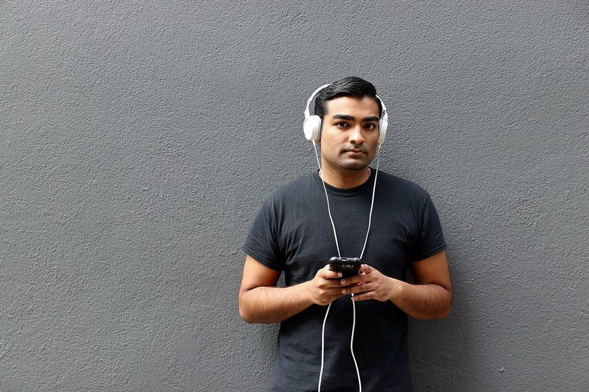 Young handsome man in black shirt on phone listening to music through headphones Alone Black Blue Jeans Cool Earbuds Grey Handsome Happy Headphones Indian Listening Man Music One Man Only Phone Portrait Smart Phone Student Tech Technology Telephone Texting Wealthy White Young Adult