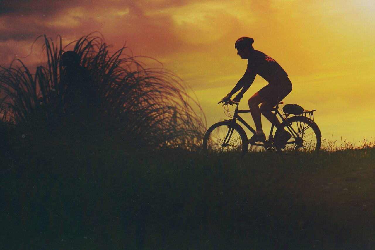 bicycle, silhouette, one person, real people, cycling, men, transportation, sunset, full length, nature, leisure activity, lifestyles, side view, land vehicle, outdoors, riding, adventure, grass, beauty in nature, mountain bike, sky, healthy lifestyle, helmet, scenics, water, headwear, day, one man only, adult, people