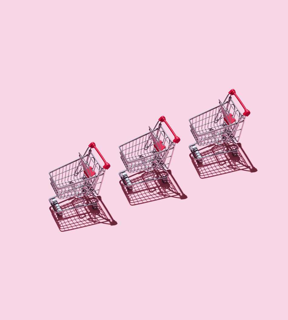 Three Shopping Carts organized over pink background Basket Cart Commerce Commercial Concept Conceptual Harsh Shadow Market Organized Organized Neatly Purchase Sale Shopping Shopping Cart Supermarket Things Organized Neatly Trolley