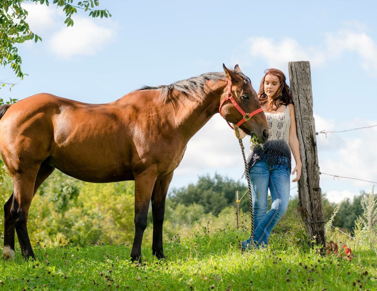 Young Woman Standing By Horse On Grassy Field Against Sky