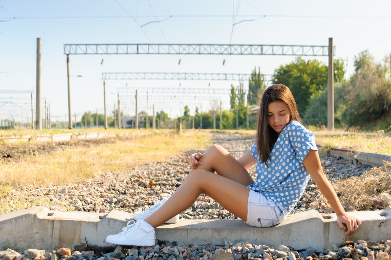 Brunette girl teenager sitting on the concrete of unfinished rail track outside the city Brunette Caucasian Countryside Day Escape Girl Horizontal Nature Outdoors People Rail Railway Relaxation Rural Shorts Sit Summer Teen Teenager Young Adult