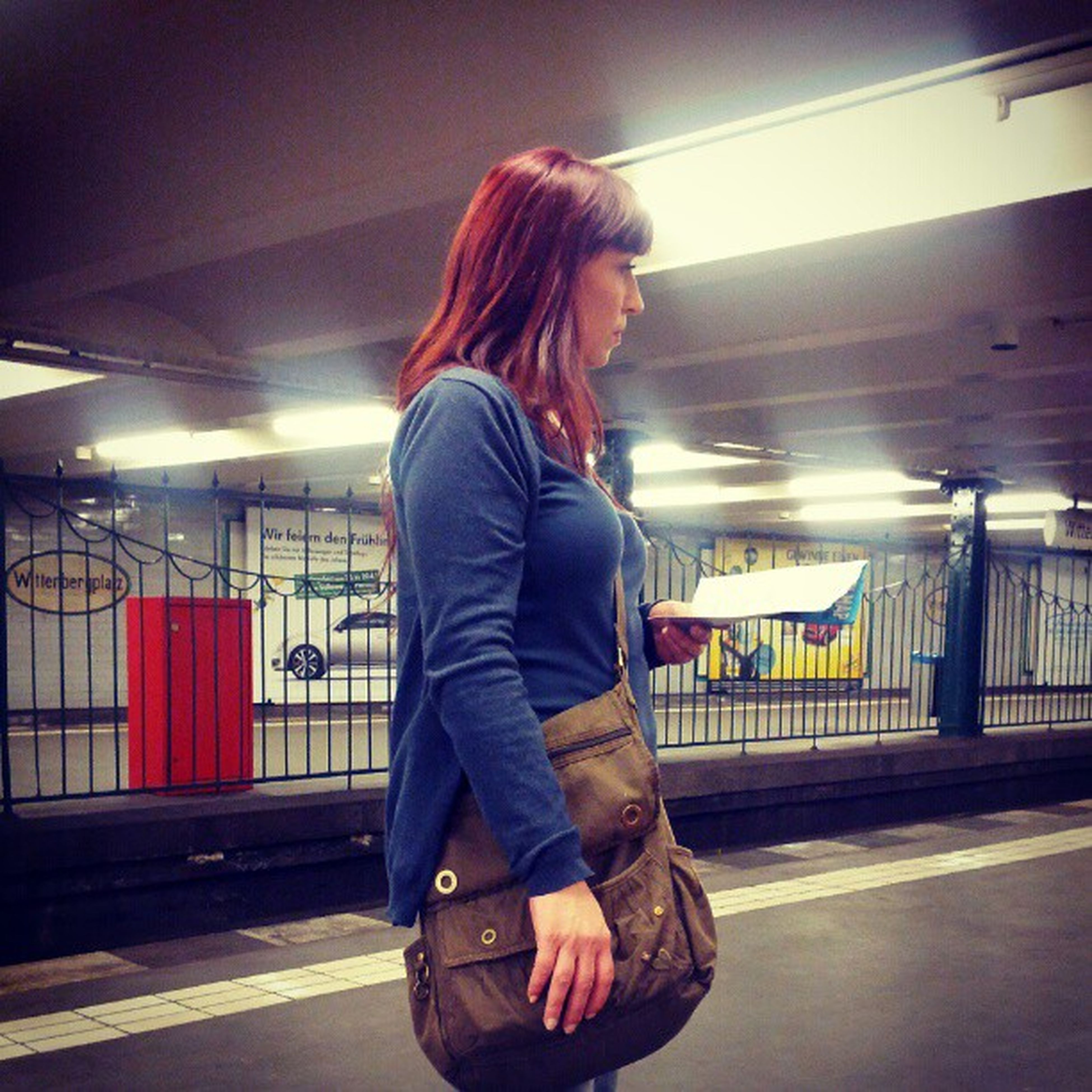 full length, casual clothing, indoors, lifestyles, standing, illuminated, three quarter length, rear view, leisure activity, railroad station platform, person, night, railroad station, young adult, front view, young women, transportation, blurred motion