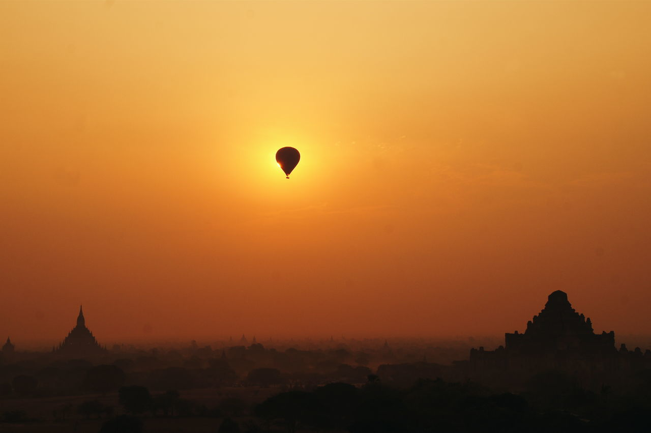 sunset, religion, silhouette, orange color, hot air balloon, spirituality, architecture, place of worship, sky, building exterior, adventure, nature, no people, outdoors, beauty in nature, built structure, clear sky, flying, tree